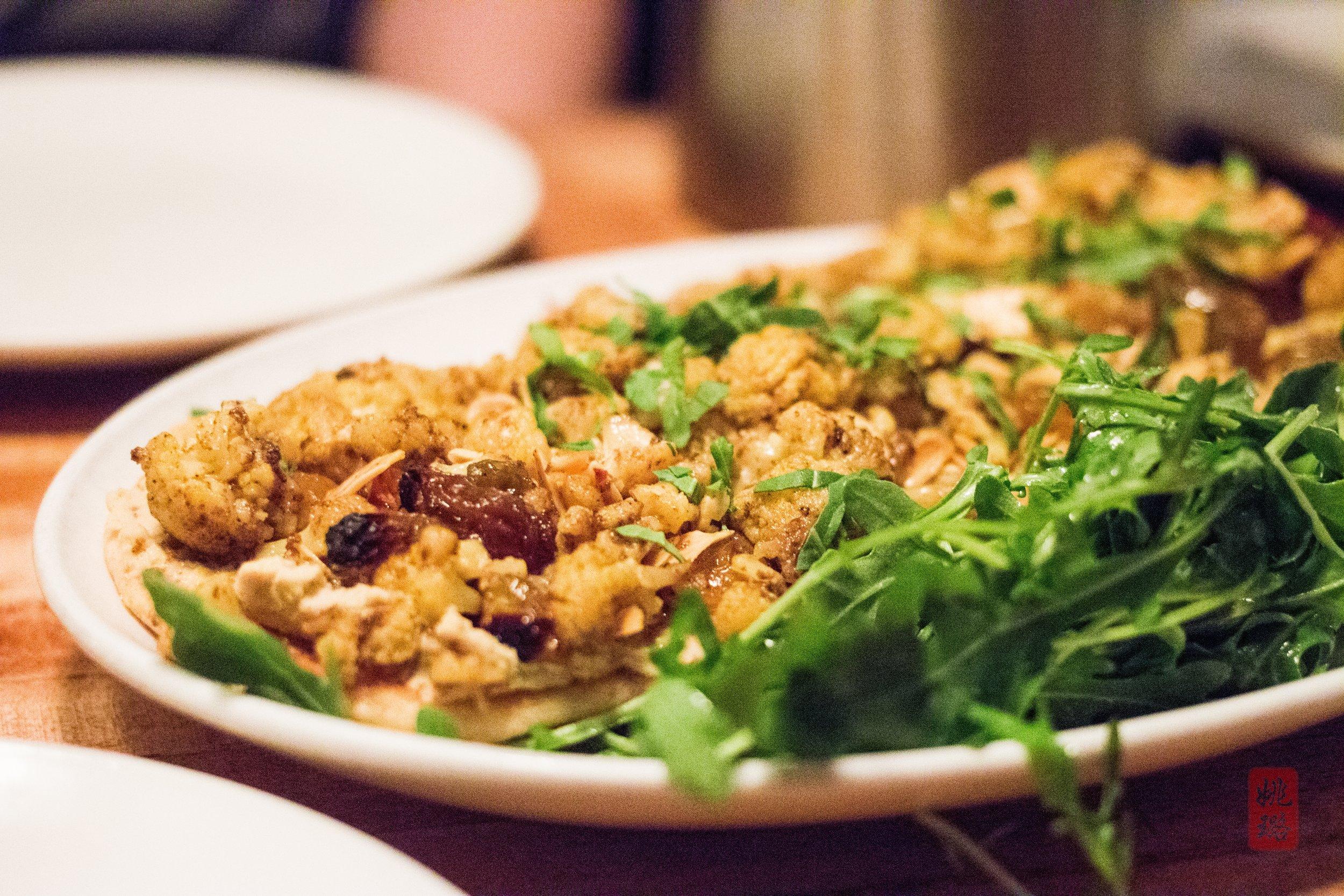 Cauliflower tartine:curry-roasted cauliflower, hummus, golden raisins, toasted almonds, and parsley on toasted naan