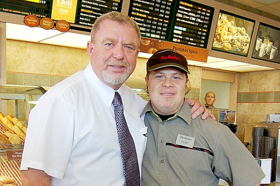 Mark Wafer with his arm around an employee at Tim Hortons. Both smiling.