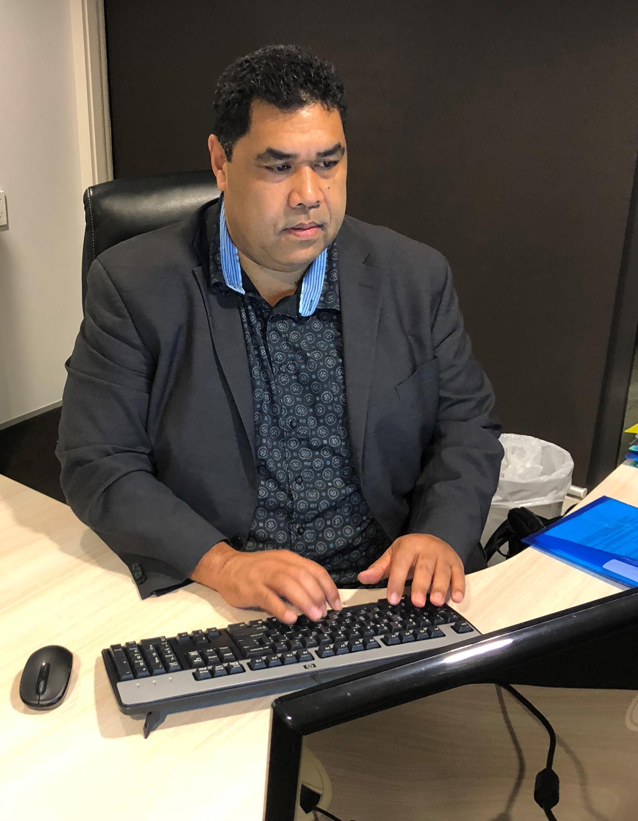 Tio at desk reporting article (2).jpg