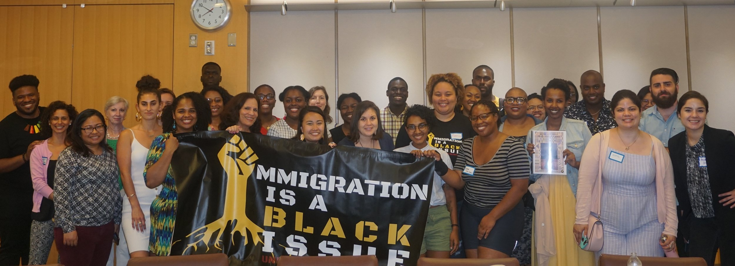 """Pictured above is a group photo of attendees from the Alive and Well Discussion Series launch, which took place in Washington DC on May 30, 2019. The people in the front row are holding a banner which says """"Immigration is a Black issue."""""""