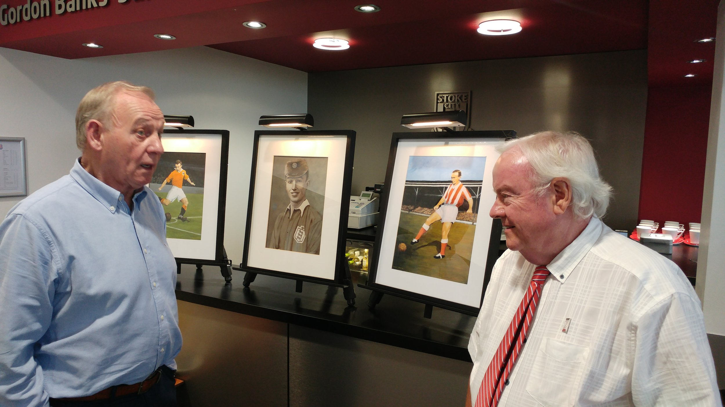 Denis Smith and Roger Horwood in conversation, in front of paintings of Sir Stanley Matthews by local artist Muriel Valentine