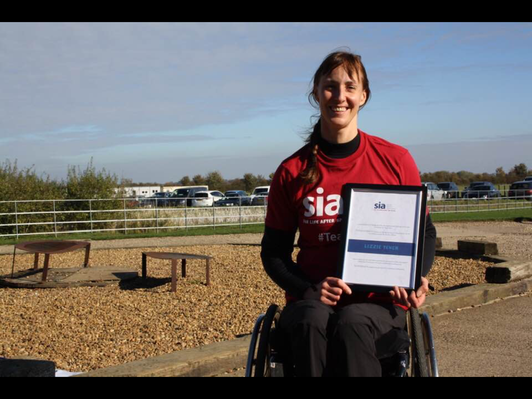Lizzie - back on the ground, proudly showing off her 'top fundraiser' certificate