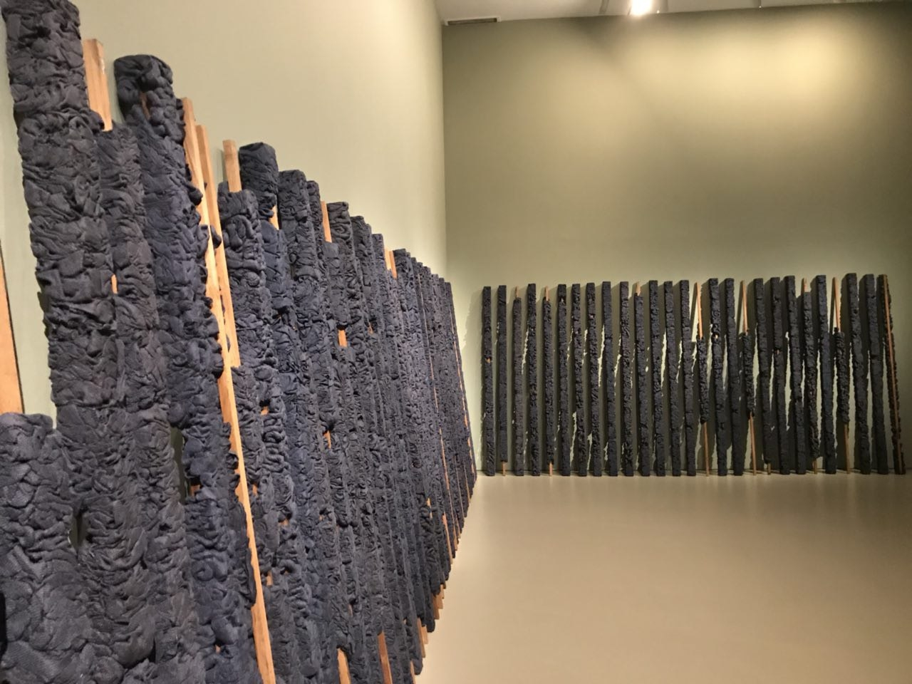 Compressed indigo jute cloths and wood, by Manish Nai, 2018.