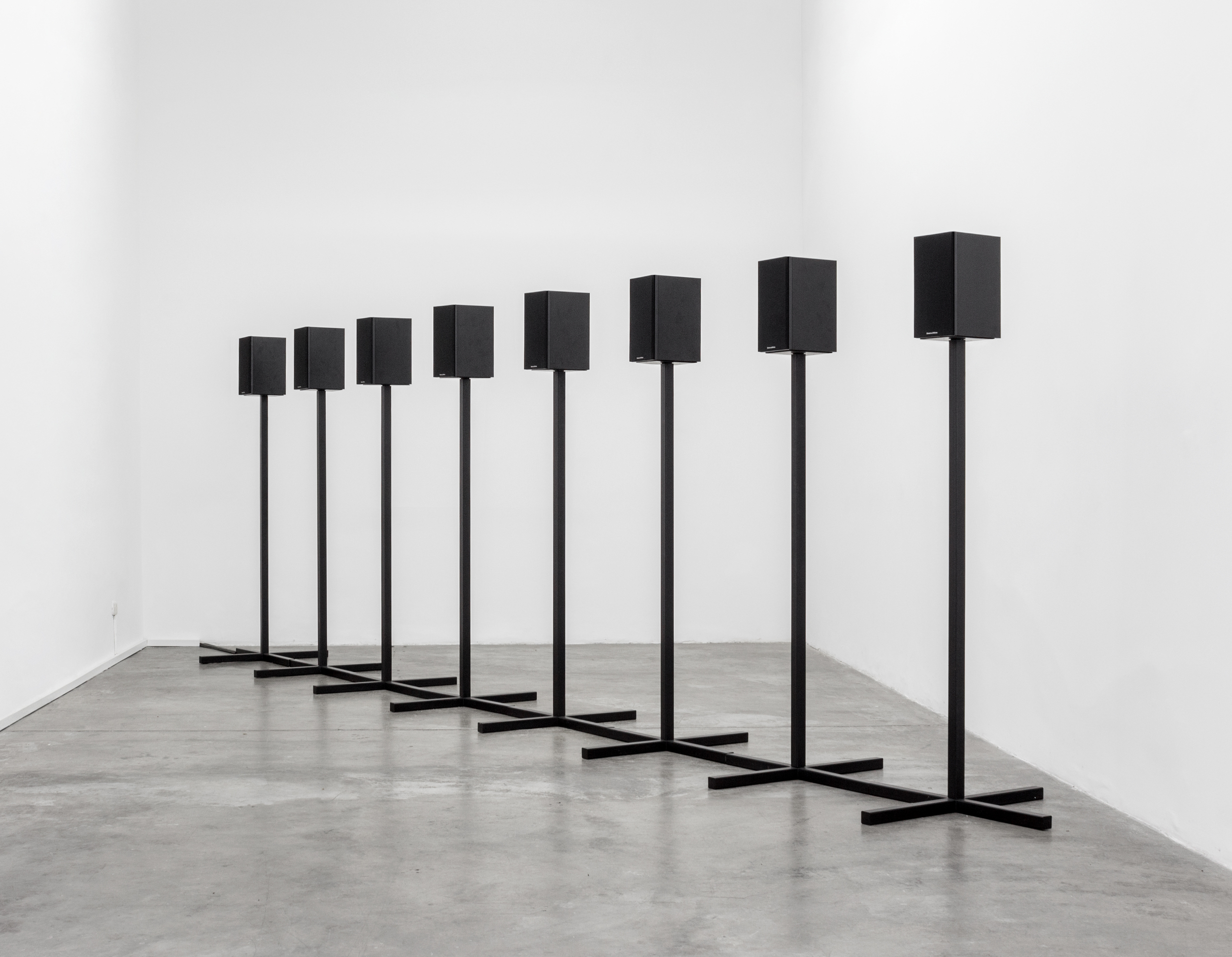 Andrea Galvani   ©   2012/2016  ,   A Cube, a Sphere, and a Pyramid #1  . Ultrasonic audio track (1 hour 20 minute loop), 8 loudspeakers, two-part custom black metal speaker stands, and amplifier. Installation view at Revolver Galeria, Lima.