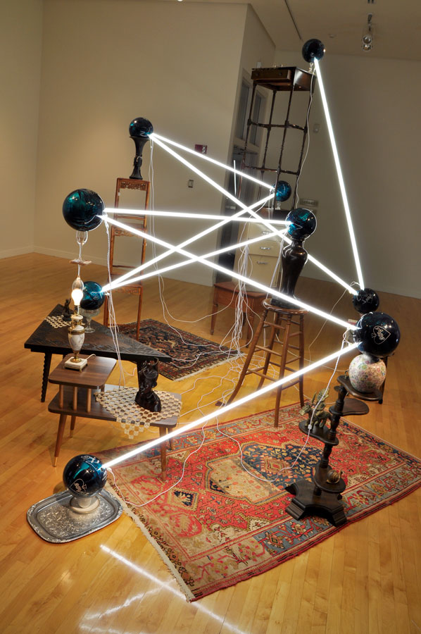 Alejandro Almanza Pereda © 2011 , S pare the rod, spoil the child . Fluorescent light bulbs, bowling balls, lamp, books, tatted doilies, textiles, wood Polynesian bust, electric cords, glassware, ceramics, wood side and coffee tables, metal tray, end tables, wooden stools, c. 17th–18th century Qing dynasty Chinese bronze libation vessel, c. early–20th century Chinese rosewood stacking tables, c. 18th century Qing dynasty Chinese bronze vase, c. 20th century, Nigerian Yoruba brass equestrian figure, c. 20th century Iranian Karaz wool rug, c. 20th century Iranian Hamadan wool rug, A.D. 1927 stone from the College of Wooster Memorial Chapel. Dimensions variable. Courtesy of the artist.