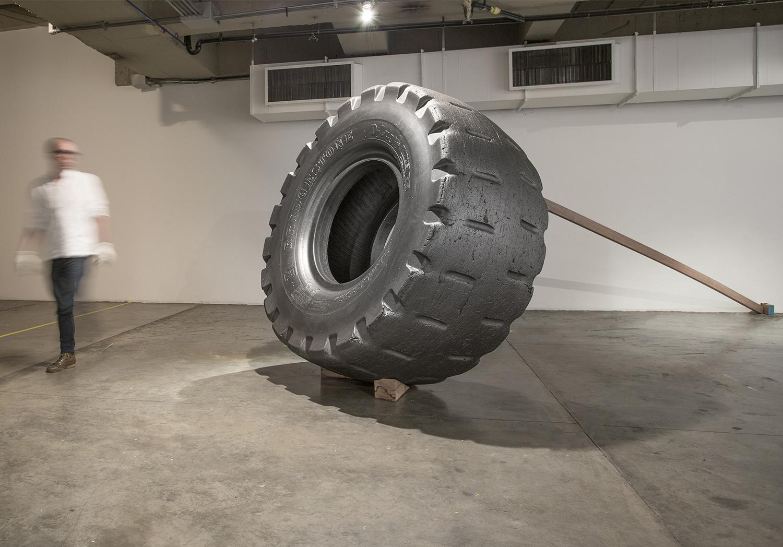 Santiago Reyes Villaveces  ©  2014 ,  Cargo Tire 35 65-33 . Wood, graphite and tire. Ø86.6 x 35.4 in (Ø 220 x 90 cm), wood beam 3.9 x 1.9 x 196 in (10 x 5 x 500 cm). Courtesy of the artist.