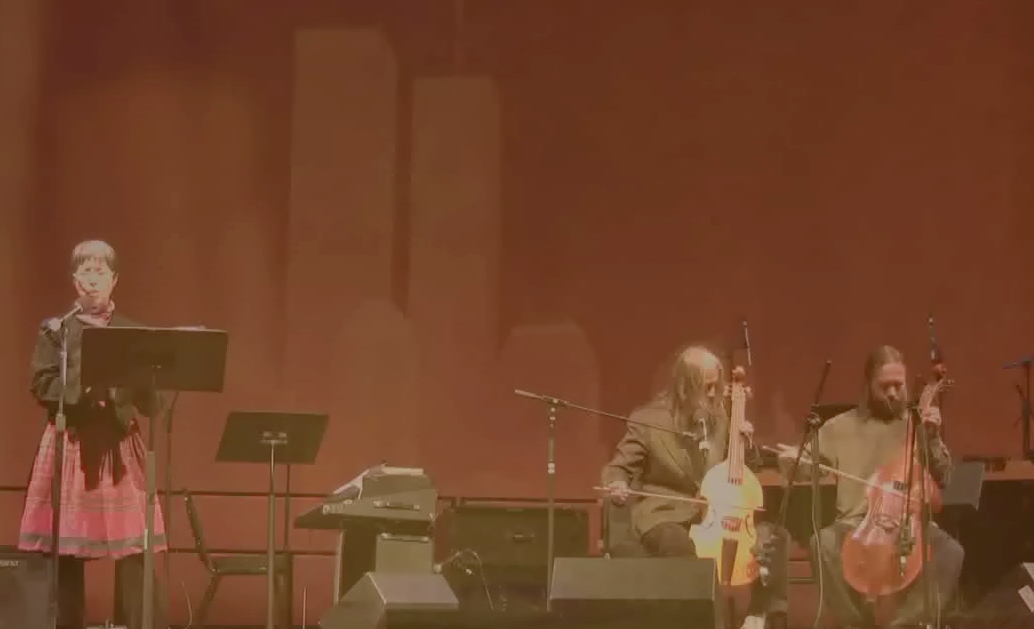 Cecilia Vicuña © 2009 ,  The Shadow of Sorrow . Video of a performance by Cecilia Vicuña, with Irene & Vojtech Havel. In a Musical Tribute to Pablo Neruda at the World Financial Center in New York City on April 15, 2009. Courtesy of the artist.