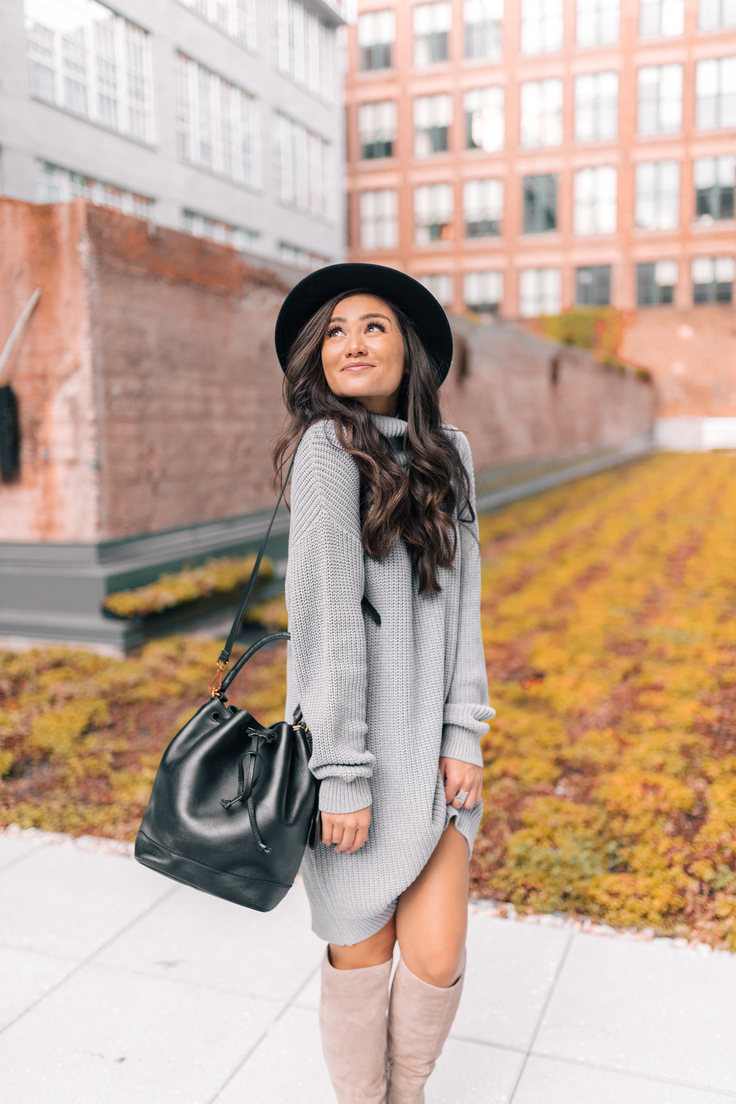 Caila Quinn Fall Fashion Gray Oversized Sweater Dress and high boots with hat