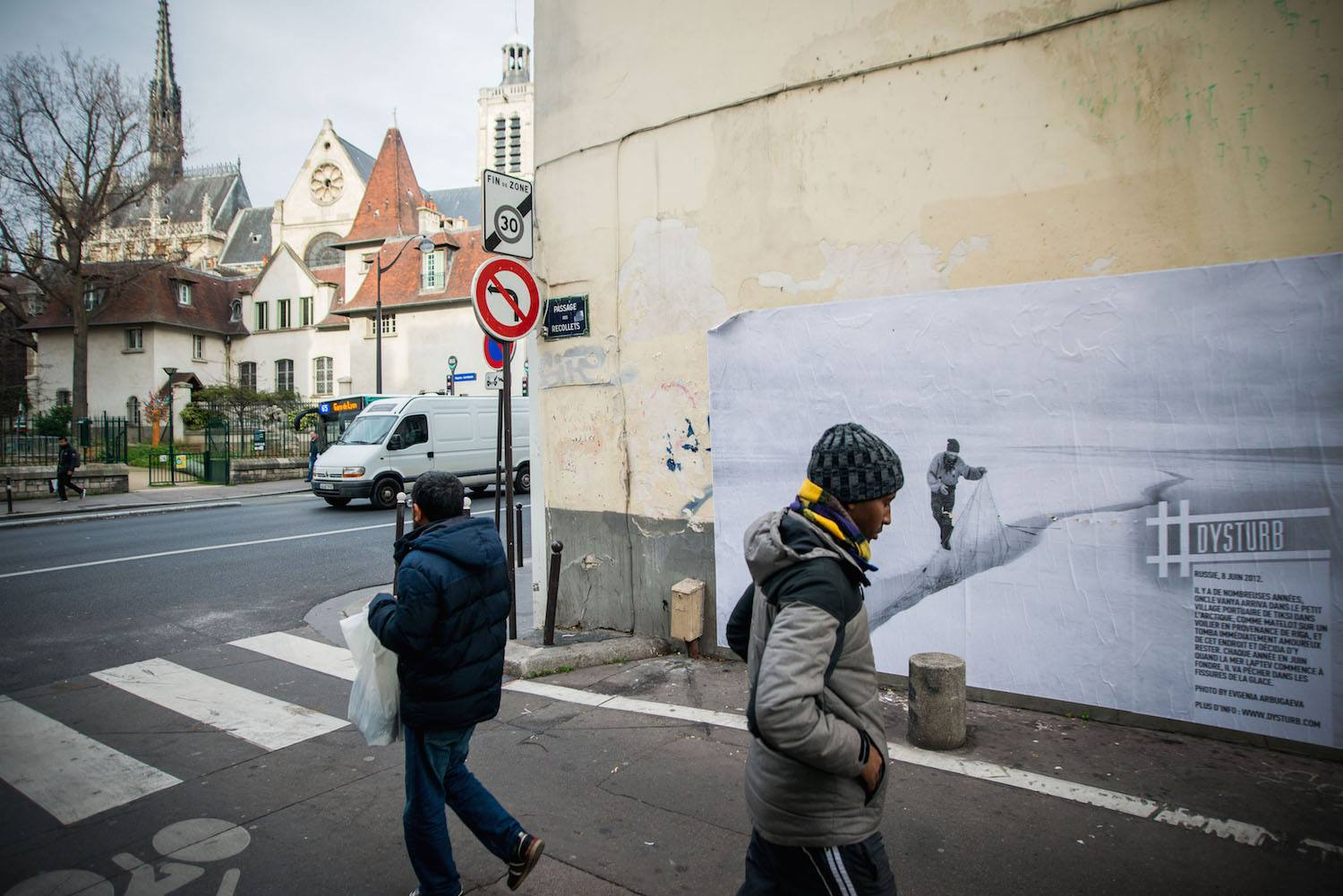 © Benjamin Girette. For COP21, we teamed up with the Magnum Foundation, Yale School of Forestry and Environ-mental Studies, NYU-ITP Students & Twillio to #reframeclimate by pasting current photojournalism in the streets of Paris. Pictured is ©Evgenia Arbugaeva's photograph which can be found on 3-5 Passage des Récollets. The caption reads: Russia, June 8th, 2012. Many years ago uncle Vanya arrived to a small Arc-tic port town Tiksi from Riga as a sailor on a ship and immediately fell in love with the place and stayed. Now every June when Laptev Sea starts to melt, he catches the moment to fish in the cracks of the ice.