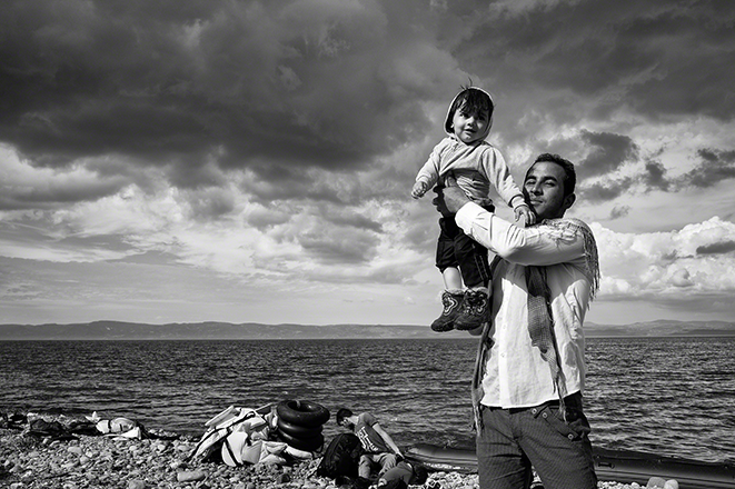 Tom Stoddart, Lesbos, Greece, 2015 A father celebrates his family's safe passage to Lesbos after a stormy crossing over the Aegean Sea from Turkey. ©Tom Stoddart