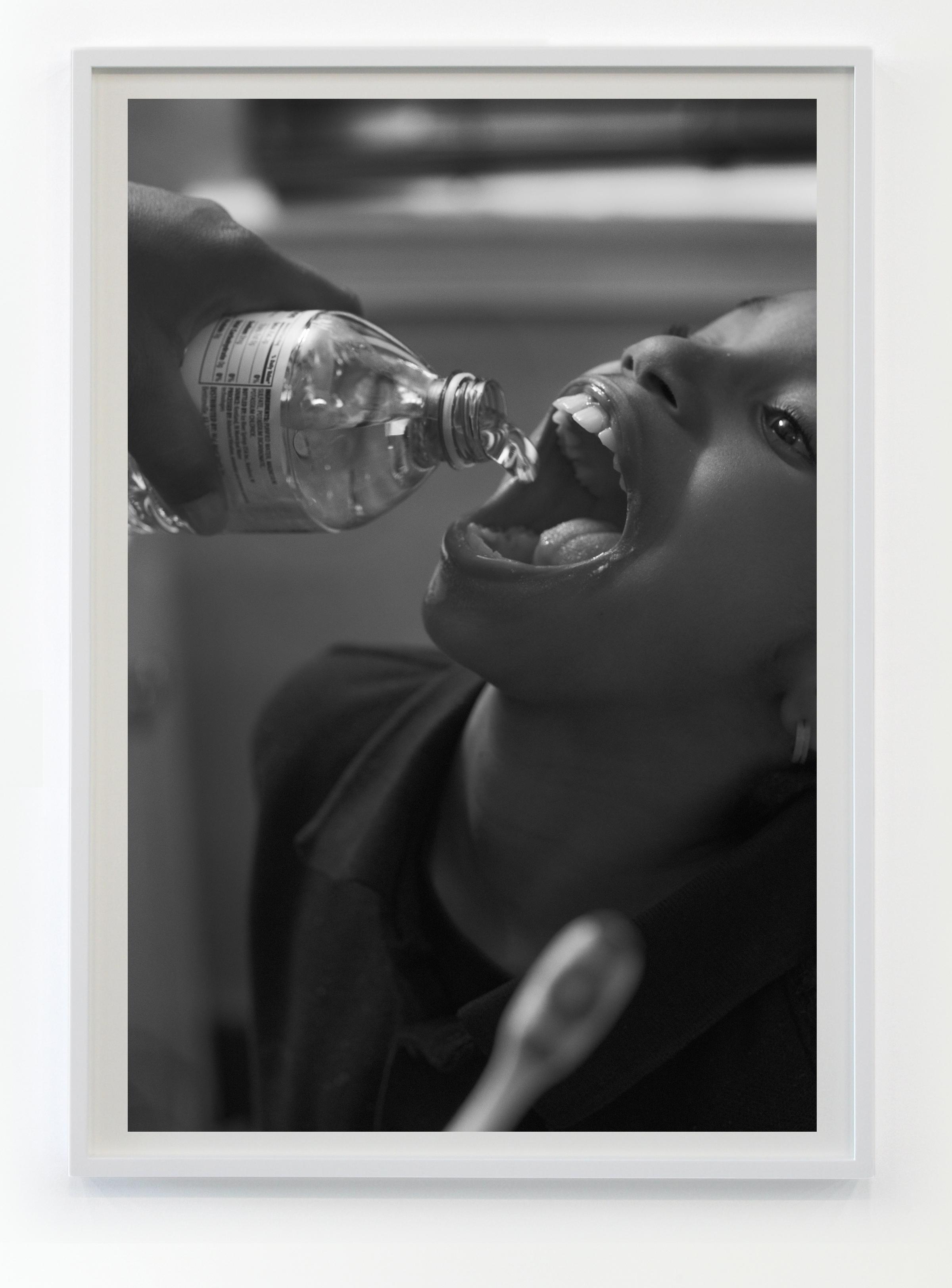 Shea Brushing Zion's teeth with bottled water in her bathroom, 2016/2017 © Latoya Ruby Frazier