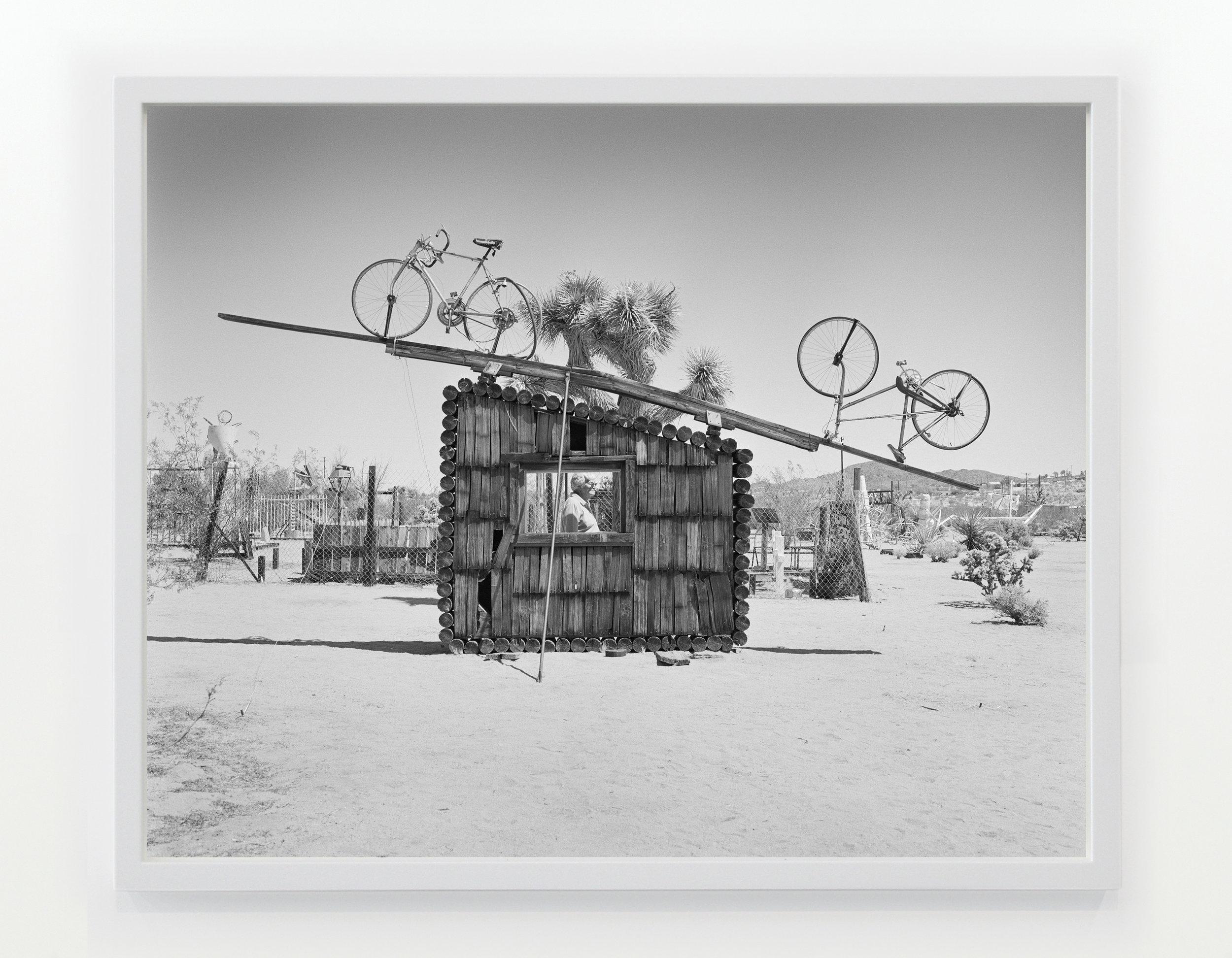 Pat Brunty the caretaker standing behind No Contest 1994, Noah Purifoy Outdoor Desert Art Museum, Joshua Tree, CA 2016/2017 © Latoya Ruby Frazier