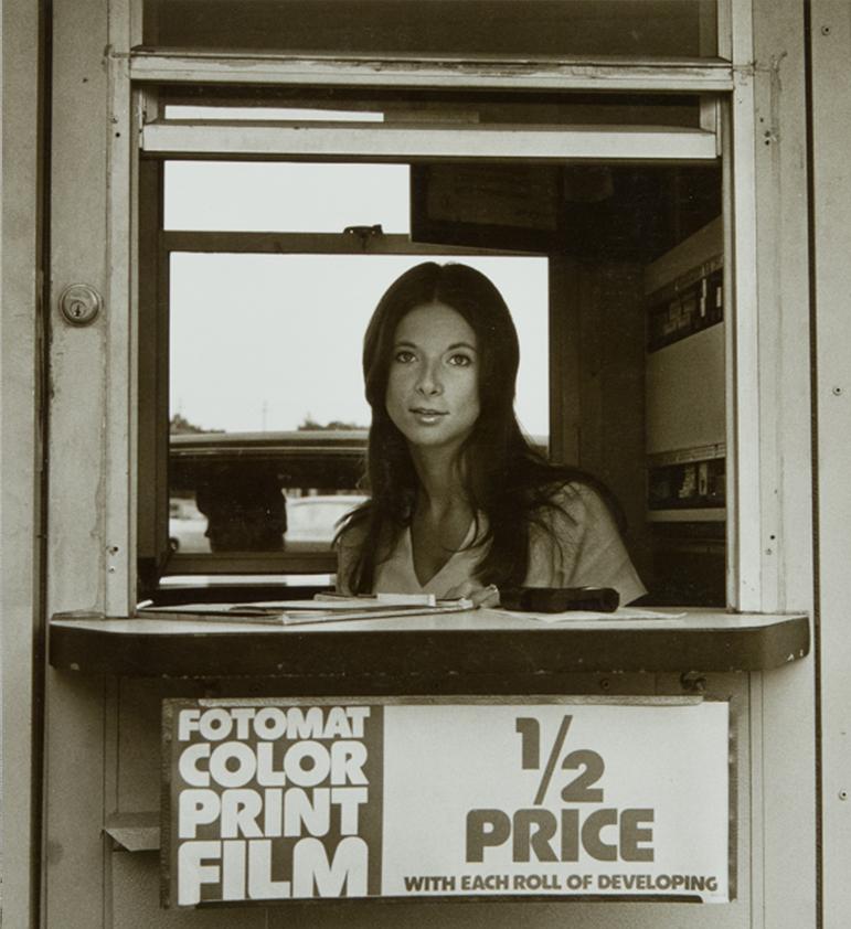 © Raymond Smith (American, born 1942), Fotomat Girl, Louisville, Kentucky, 1974, gelatin silver print, Lent by the artist