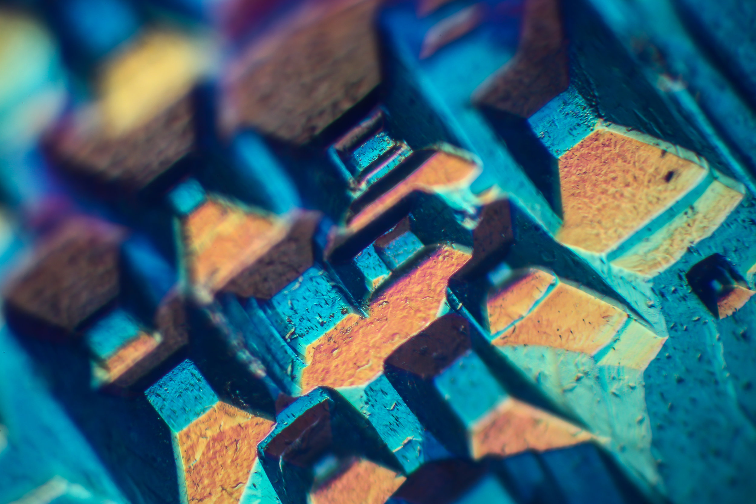 This image shows the surface of a beryl crystal. This was photographed using Differential Interference Contrast microscopy. The horizontal field of view is 1.2mm across.© Nathan Renfro