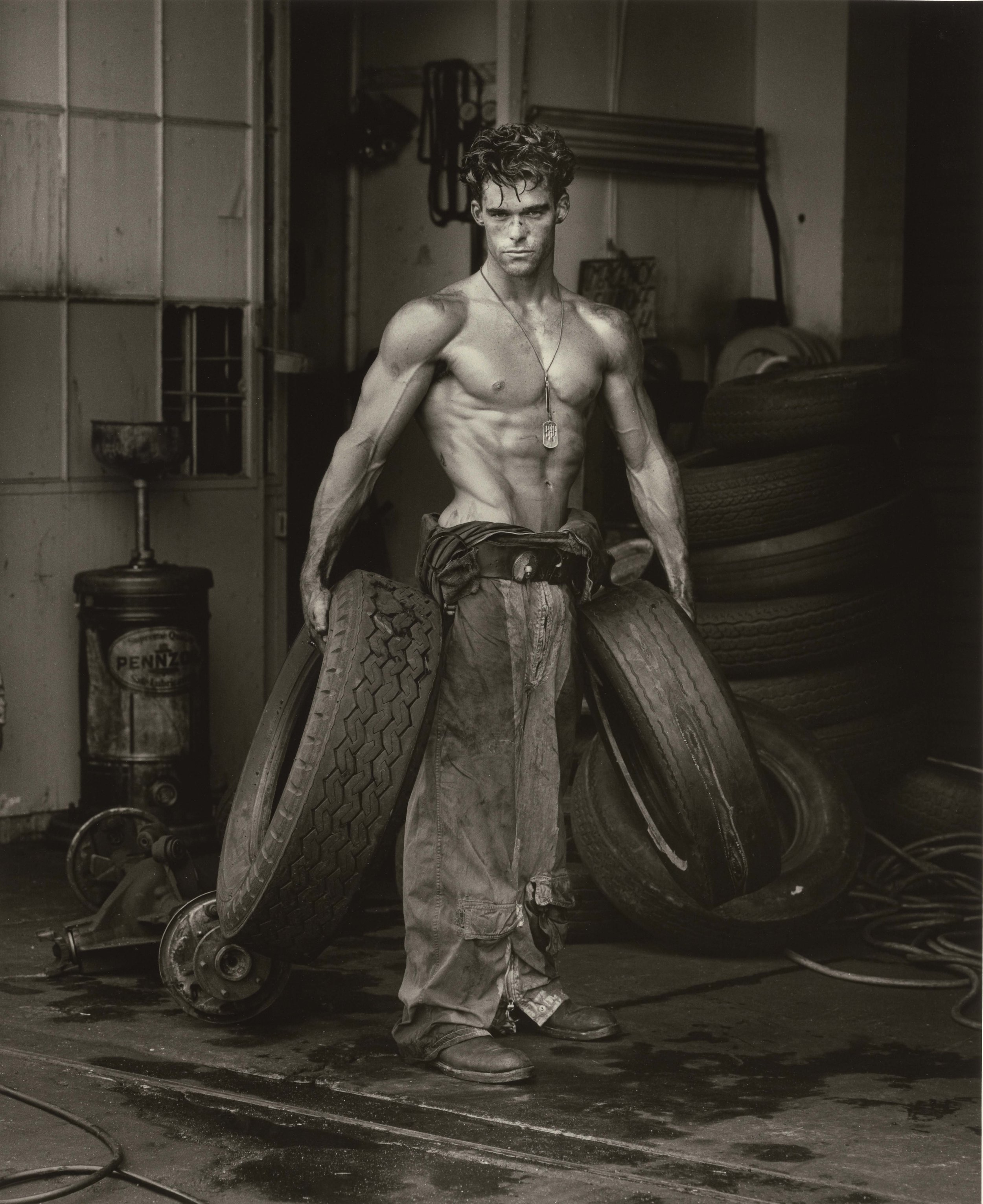 HERB RITTS (American, 1952–2002),  Fred with Tires, Hollywood , 1984. From the Body Shop series. Gelatin silver print, 47.1 × 38.6 cm (189⁄16 × 153⁄16 in.) Los Angeles, J. Paul Getty Museum. Gift of Herb Ritts Foundation, 2011.18.25. © Herb Ritts Foundation