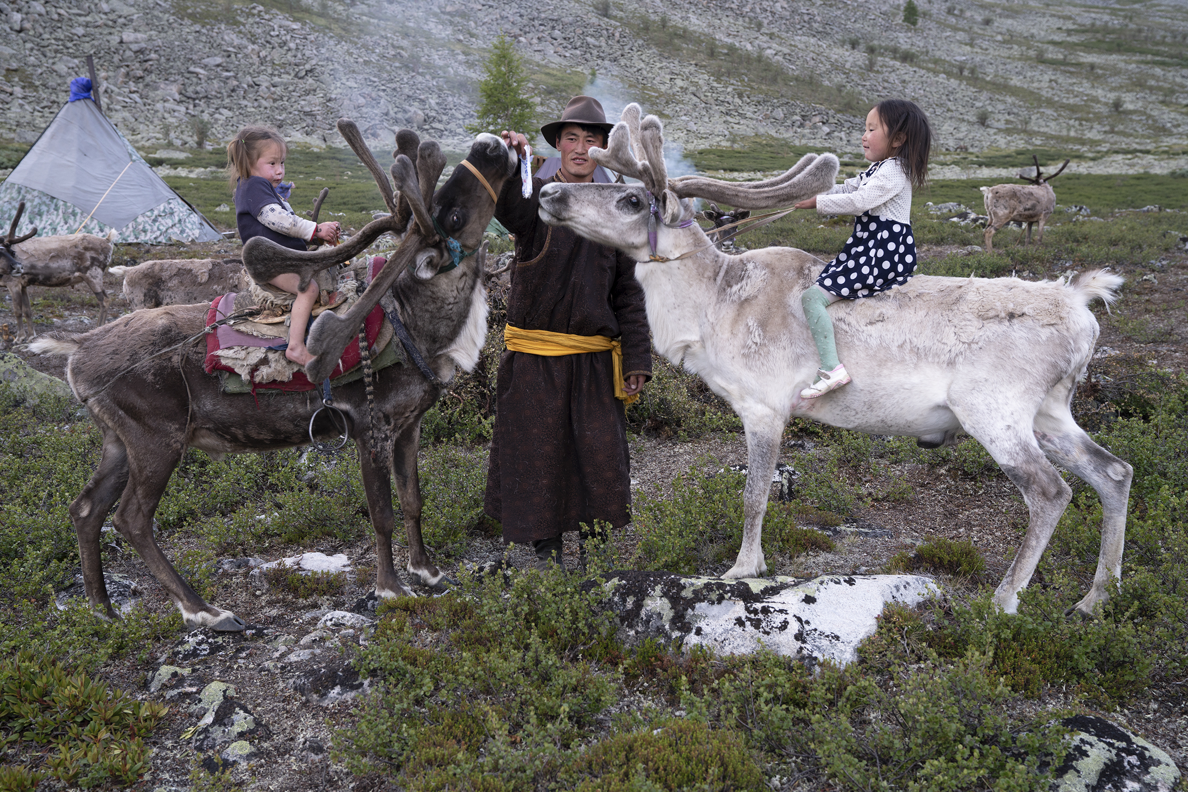 Ganbat was a man in love with his two children, Emujiin and Temujin and way of life. Here he is offering a salt lick to the reindeer. © Meghan Boody
