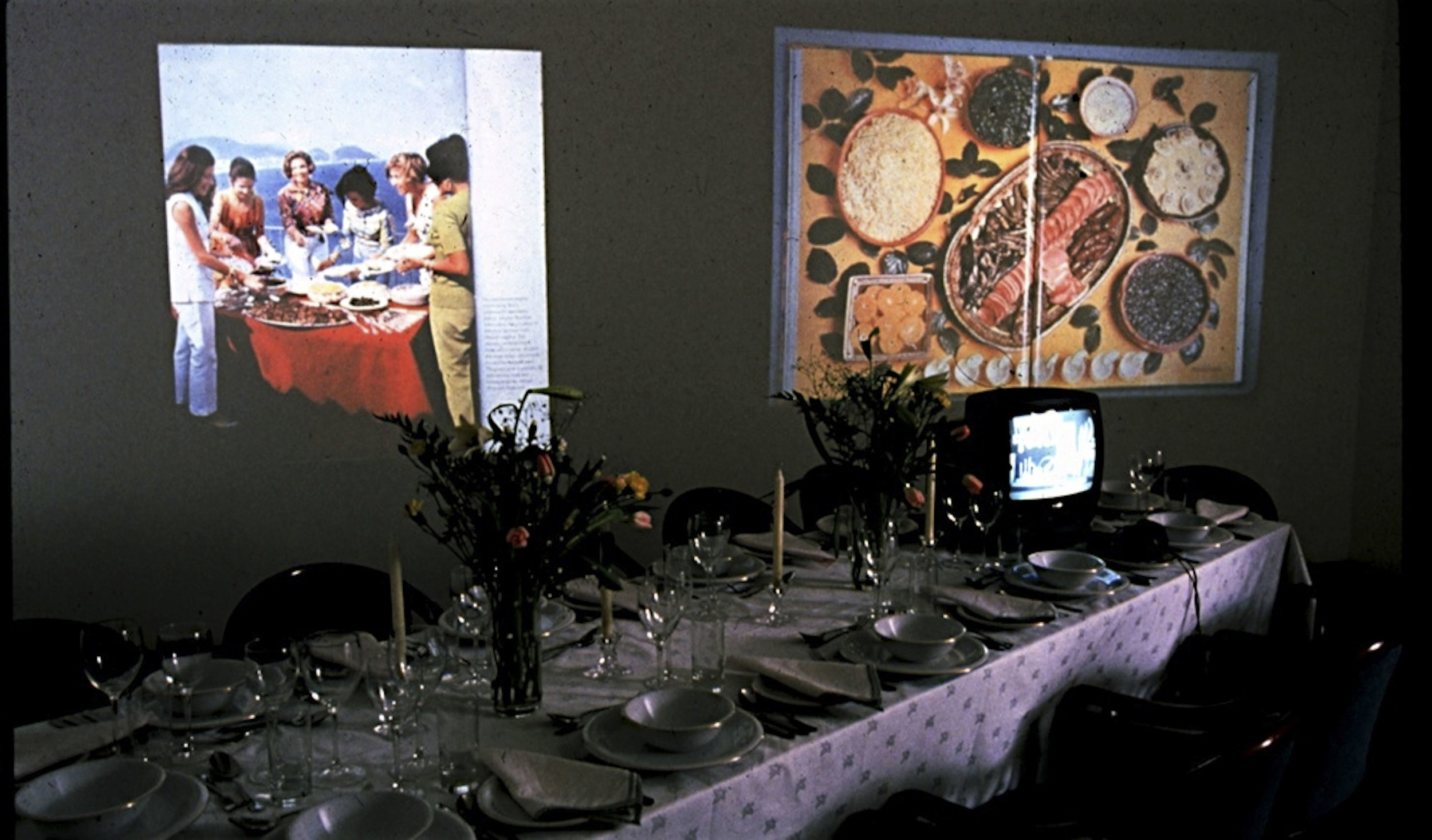 Martha Rosler, A Gourmet Experience, 1974, installation with banquet table, video, slide projections, audio, books, cookbook readings, and prints of the food novel A Budding gourmet. Artwork © Martha Rosler
