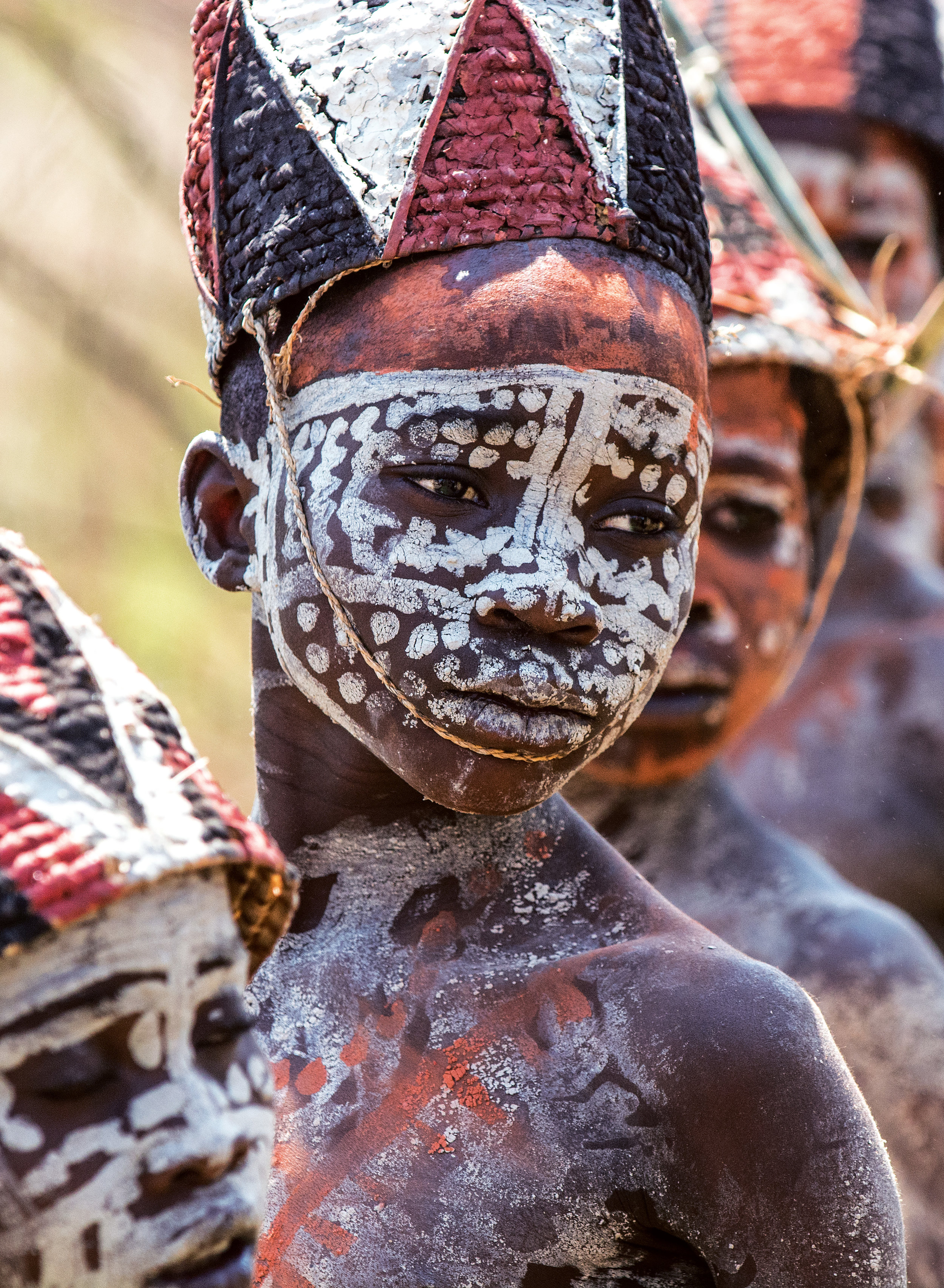 The boys have graduated from their Mukanda initiation, wearing woven hats painted with ocher and charcoal, their bodies covered in chalk. © African Twilight: The Vanishing Cultures and Ceremonies of the African Continent by Carol Beckwith and Angela Fisher, Rizzoli, 2018.
