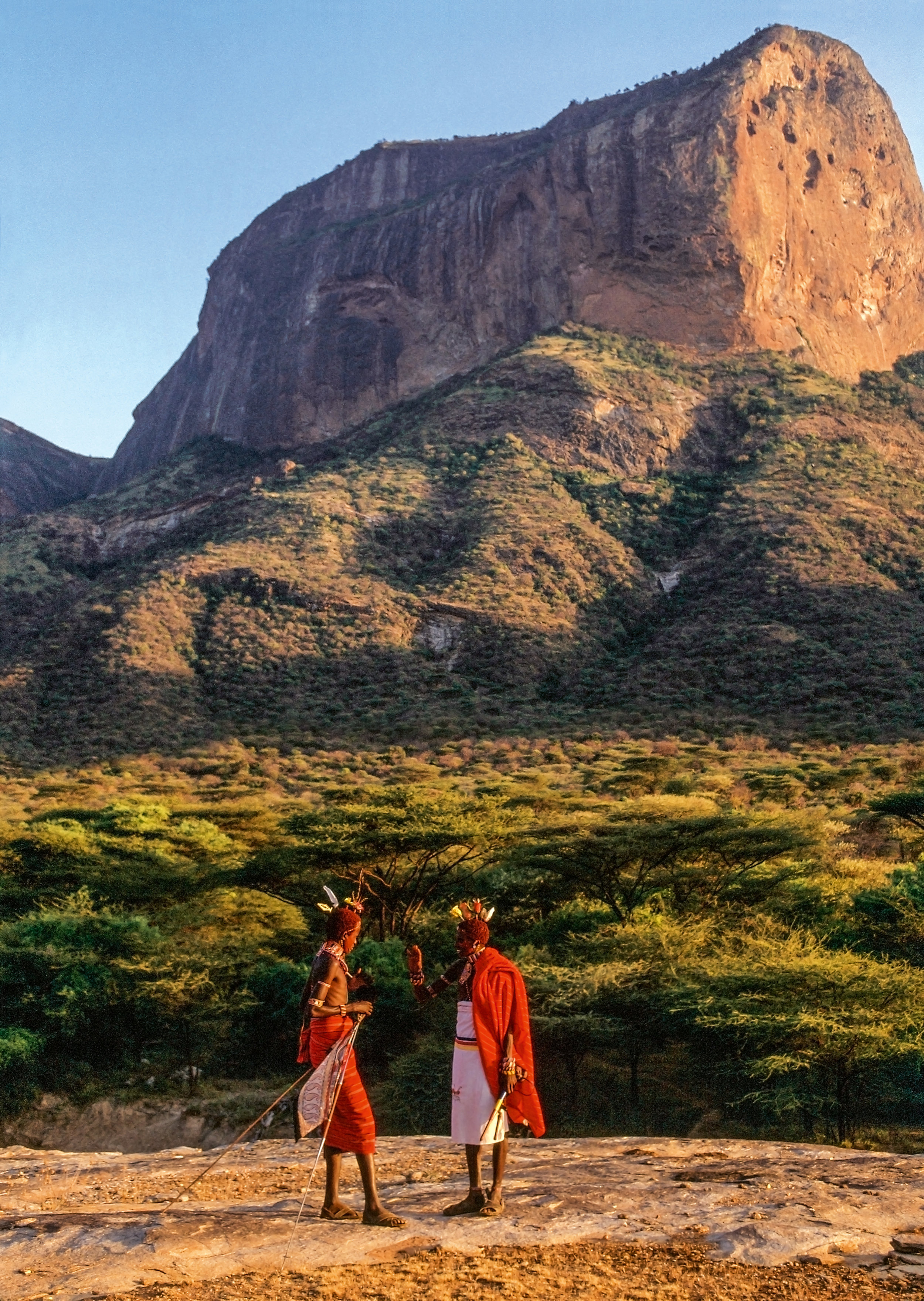 Two Tribal warriors, members of a sub-clan of the Rendille who have intermarries with the Samburu, converse in the valley of Mount Poi. © African Twilight: The Vanishing Cultures and Ceremonies of the African Continent by Carol Beckwith and Angela Fisher, Rizzoli, 2018.