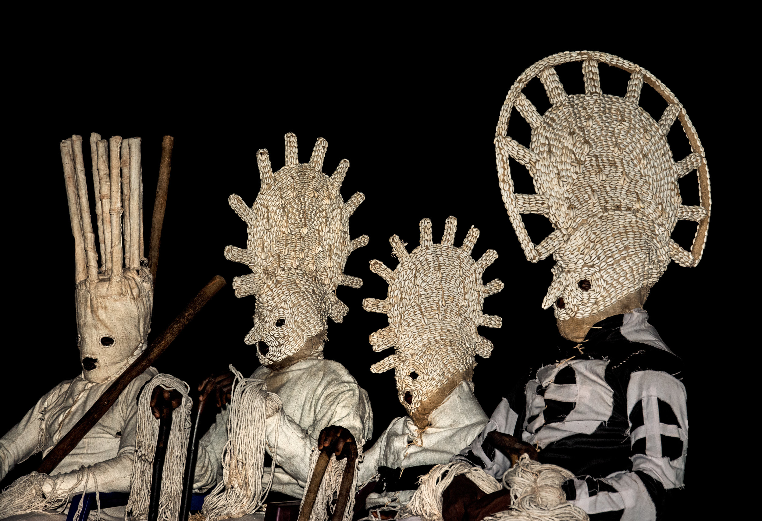 : Lunar masks appear in painted textile bodysuits, some with rope fringed headdresses and others with elaborate cowrie-shell-studded headpieces. The cowrie shell is a powerful symbol of female fertility. These masks come out in April to thank the gods for the fertility of young women. © African Twilight: The Vanishing Cultures and Ceremonies of the African Continent by Carol Beckwith and Angela Fisher, Rizzoli, 2018.