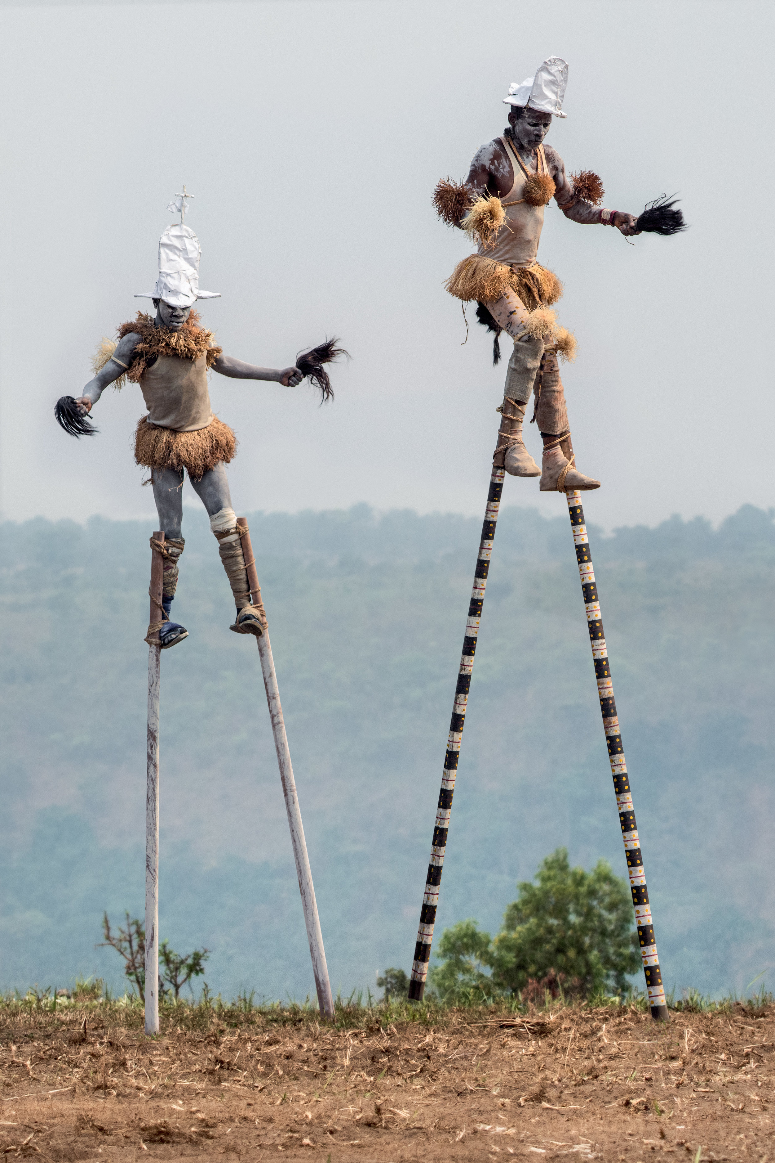 """Tu-gangonga stilt dancers called, """"Tall Men Walking,"""" come frothier village to entertain the chief. © African Twilight: The Vanishing Cultures and Ceremonies of the African Continent by Carol Beckwith and Angela Fisher, Rizzoli, 2018."""