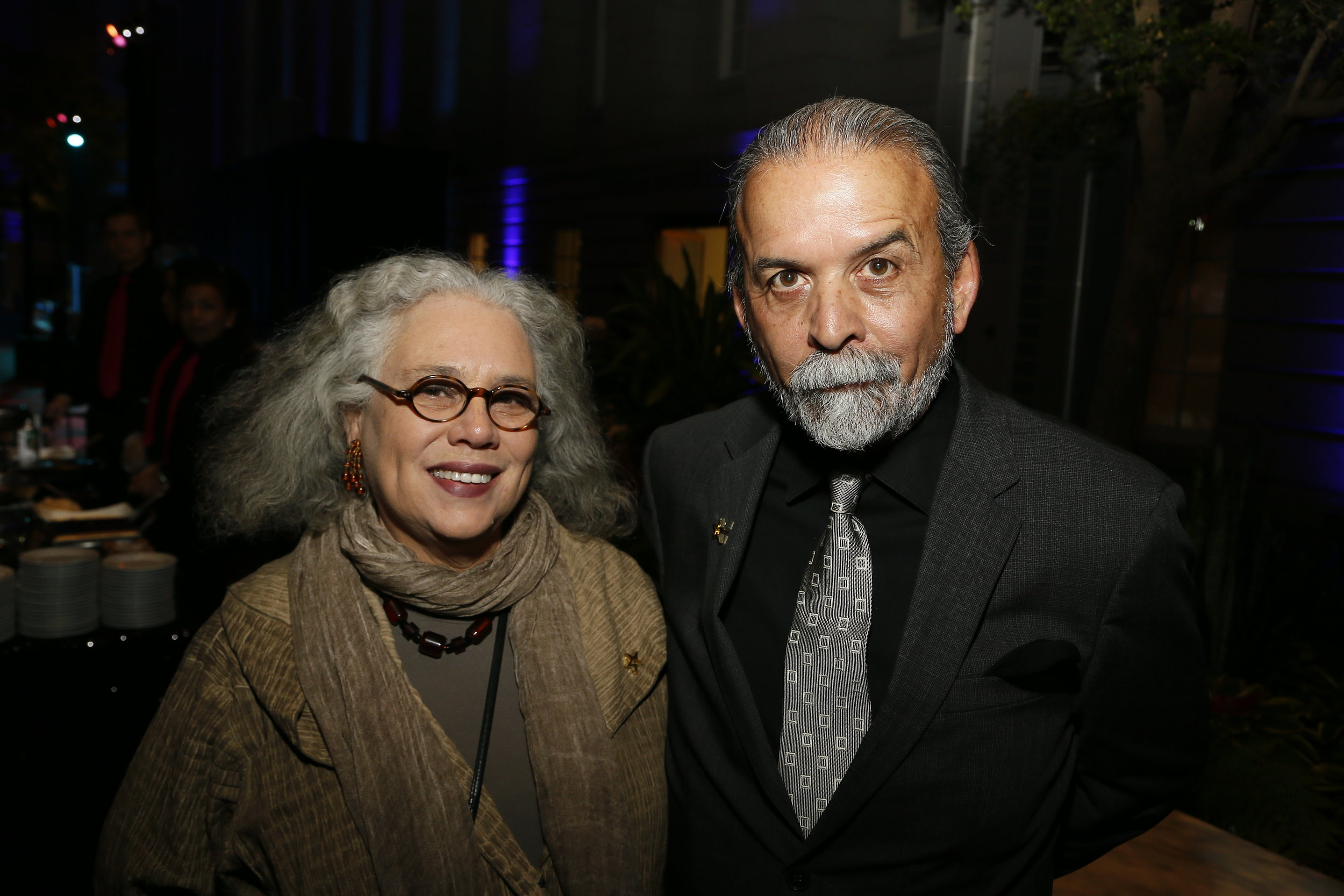 "Artist Alison Saar, left, and artist Harry Gamboa, Jr., right, attend the ""Face Forward Artist Party"" at the Smithsonian's National Portrait Gallery on Saturday, November 10, 2018, in Washington.  ©Photo by Paul Morigi/AP Images for National Portrait Gallery)"
