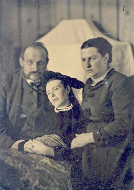 Victorian-era photo showing a family with their deceased daughter