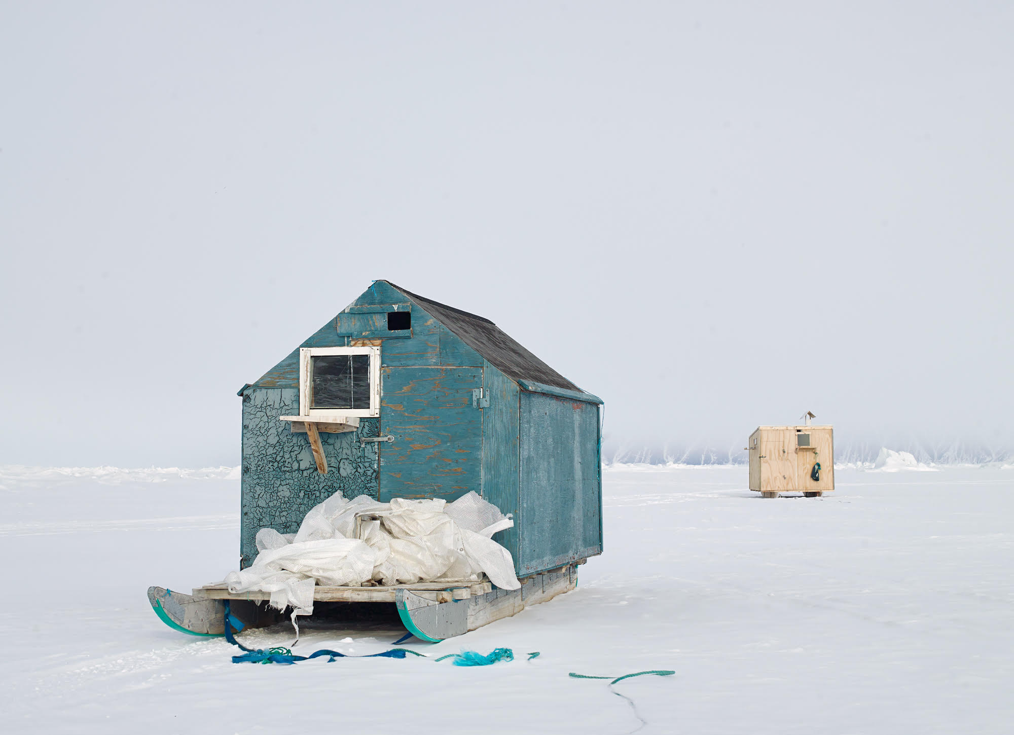 """""""Sila Fishing Houses"""", © Corina Gamma,  Fishing Huts on the Sea Ice #1 , Qaanaaq, Greenland 2018 [Fishing huts are used as temporary shelter during ice fishing. They are transported by sled after the sea ice has firmly formed, and brought to the sites for the fishing season.]"""