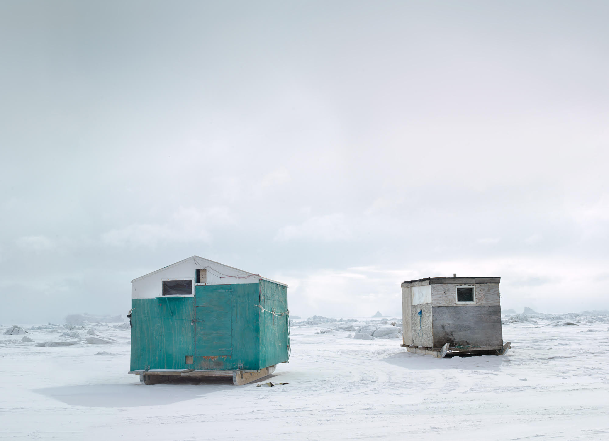 """""""Sila Fishing Houses"""", © Corina Gamma,  Fishing Huts on the Sea Ice #2 , Qaanaaq, Greenland 2018 [Fishing huts are used as temporary shelter during ice fishing. They are transported by sled after the sea ice has firmly formed, and brought to the sites for the fishing season.]"""