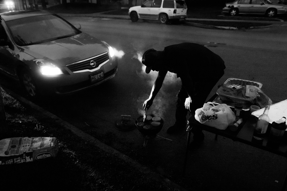 """Despite a community event being postponed, a man grills burgers on a Dolton street. """"We're still going to be out here!"""" he said, as more of his friends and family arrived. © Sebastián Hidalgo"""