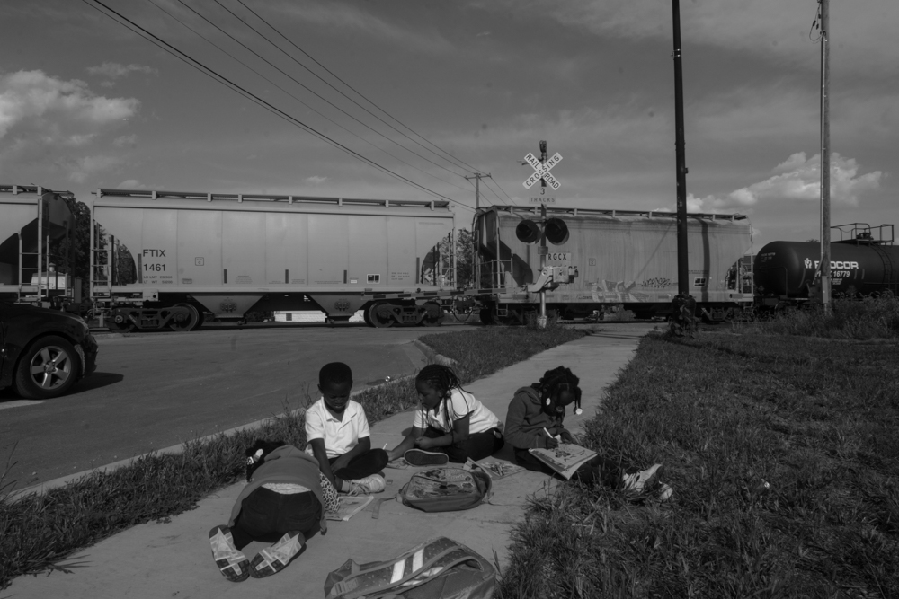 For more than two hours, a stopped freight train blocked an intersection on the border between Riverdale and Dolton in the south suburbs. Trying to get home after school, children began to do their homework as they waited for the train to clear. © Sebastián Hidalgo