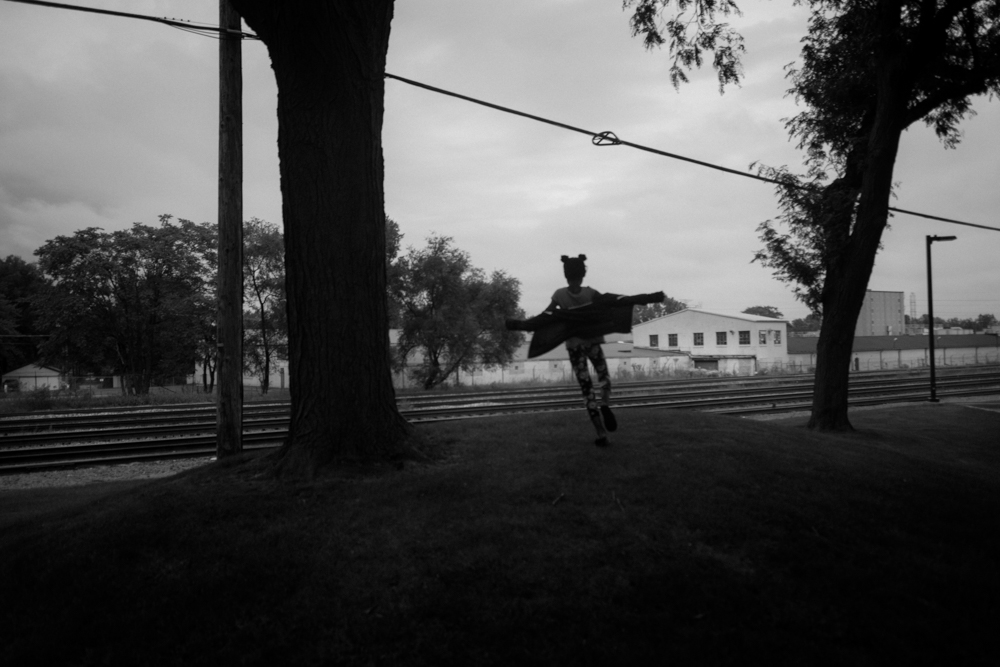 Outside the Dolton Public Library, a young girl dances on an early evening in October. Freight tracks slice through dozens of Chicago area suburbs, including Dolton. But the inconvenience in Dolton is extreme, with trains often halting and blocking intersections for hours. © Sebastián Hidalgo