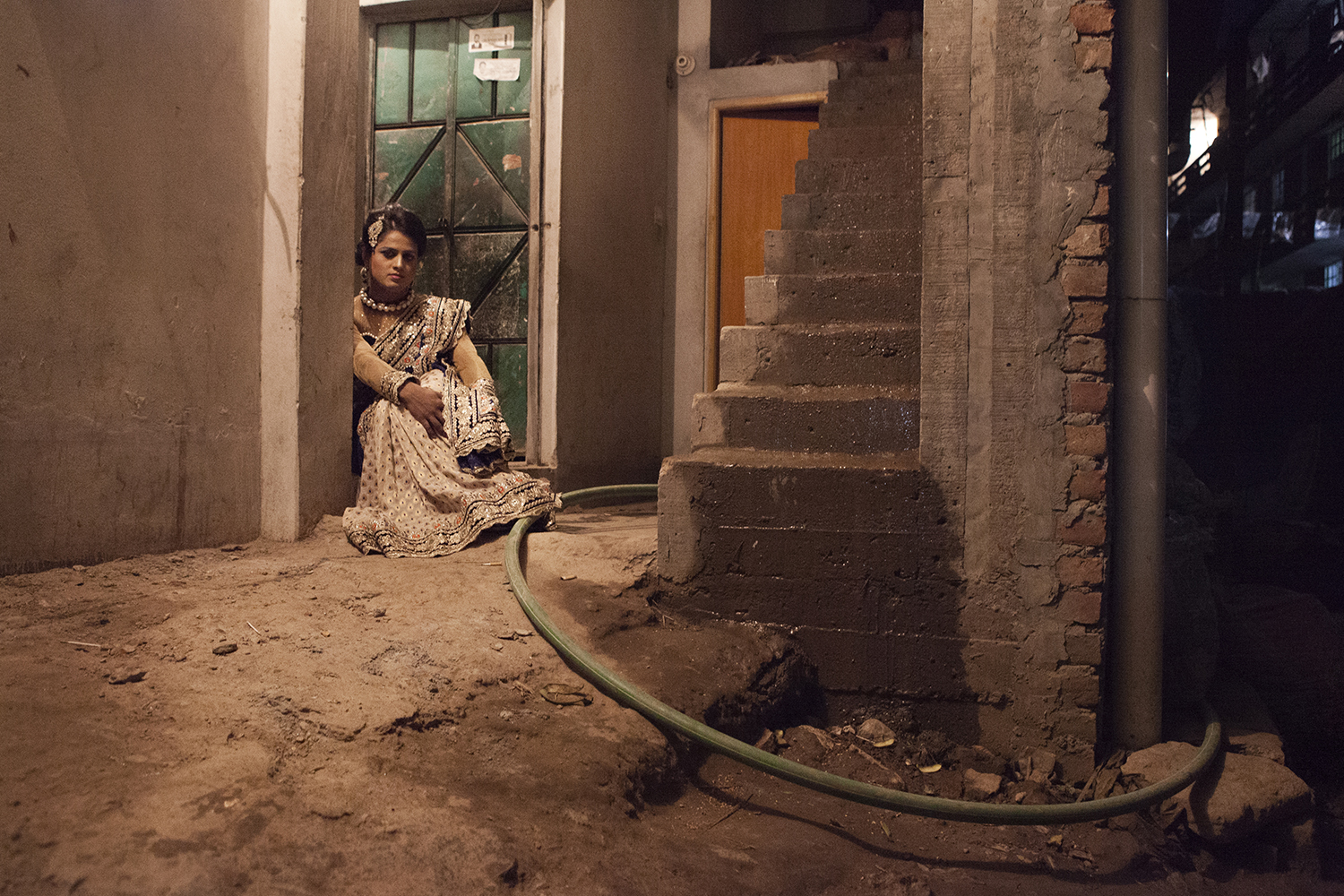 Nadim, 24 years old. She waits for a customer at the door of her home and poses for a photo. Dhaka.  © Raffele Petralla