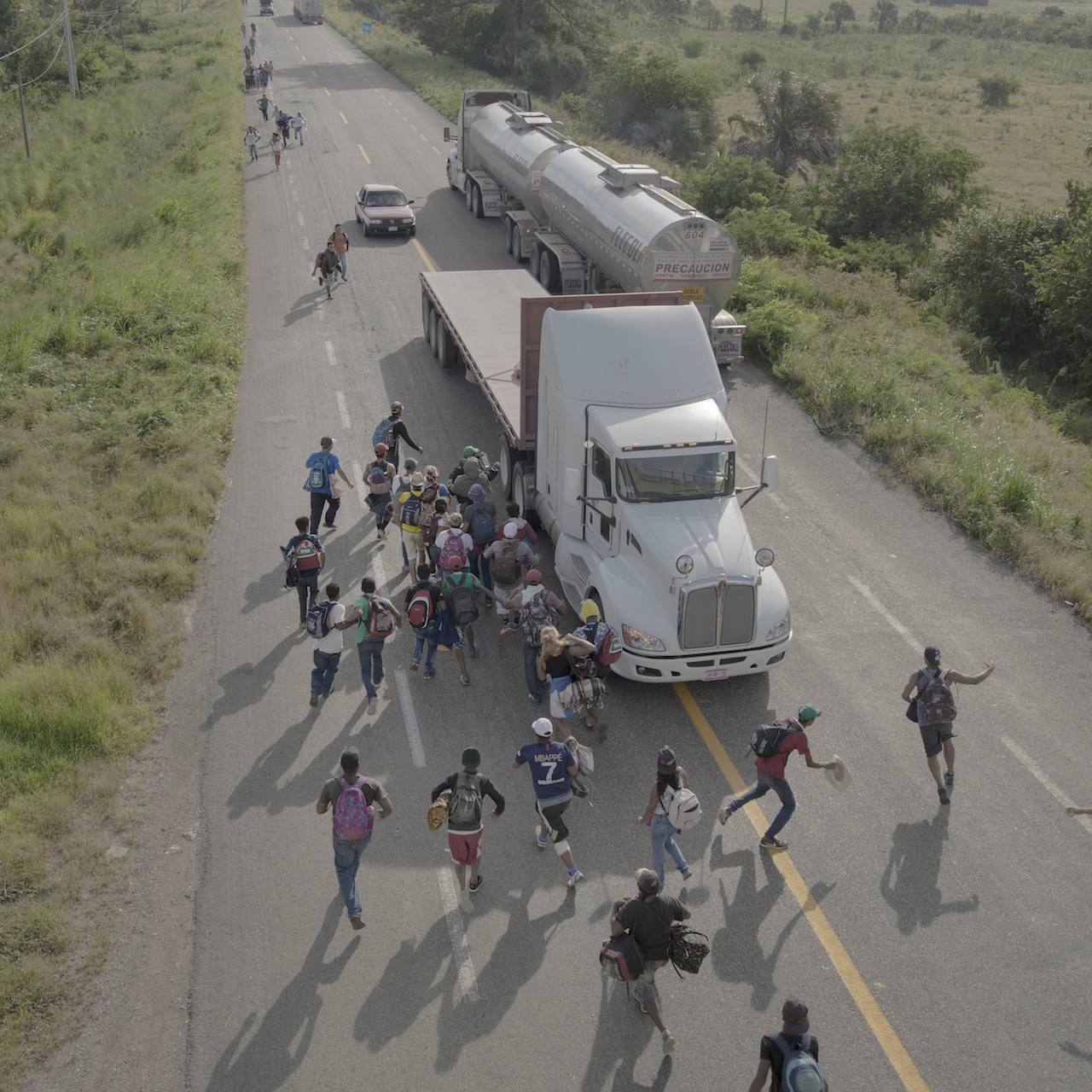 People run to a truck that has stopped to give them a ride, outside Tapanatepec, Mexico, on 30 October 2018. Some drivers charged to give travelers a lift for part of the way, but most offered services free as a sign of support. © Pieter Ten Hoopen, Agence Vu/Civilian Act