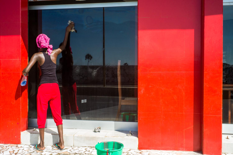 A woman cleaning a shop window in Dakar. © Werner Mansholt