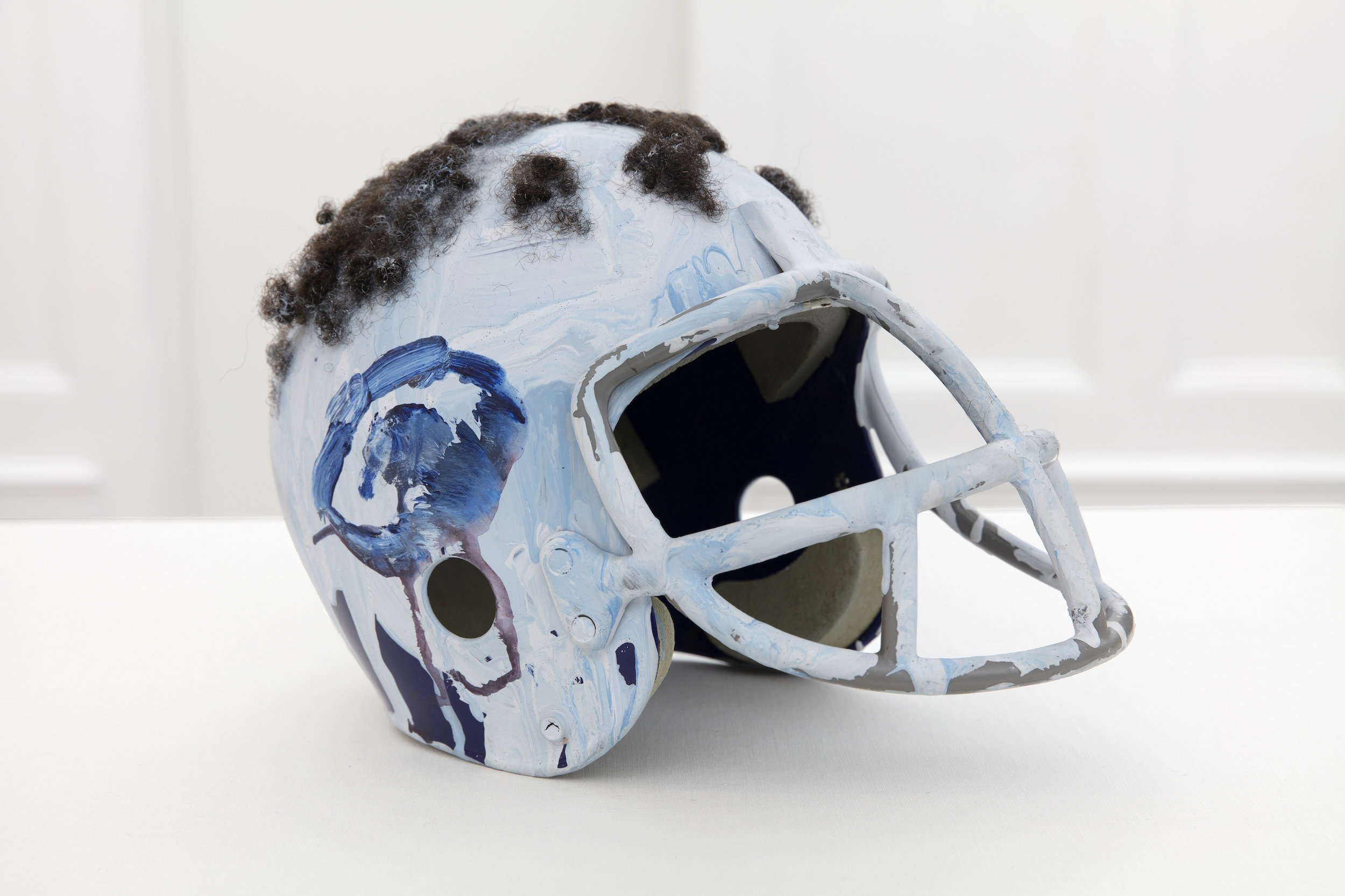 JEAN-MICHEL BASQUIAT,  Untitled (Football Helmet),  c. 1981-1984. Mixed media including acrylic and human hair on football helmet. 9 x 8 x 13 inches. JMBQ81.004 ©2019 The Andy Warhol Foundation for the Visual Arts, Inc. / Licensed by American Rights Society (ARS), New York. ©The Estate of Jean-Michel Basquiat / ADAGP, Paris/ ARS, New York 2019.