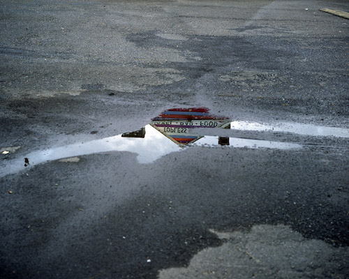 "Lisa Kerezsi. ""Topless bar reflected in puddle, Doylestown, Pennsylvania"", 2010. Archival Pigment Print. Courtesy of the artist and Yancey Richardson."