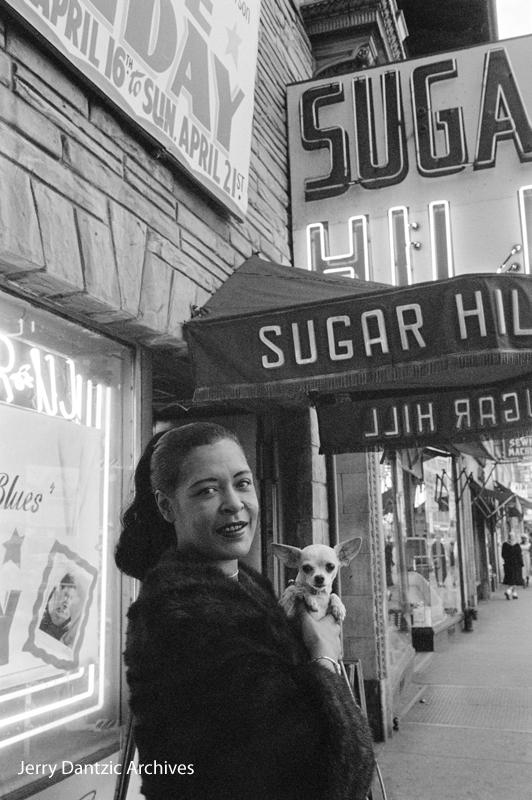 Jerry Dantzic, Billie Holiday holding her pet Chihuahua, Pepi, in front of Sugar Hill, Newark, New Jersey, April 18, 1957. © 2017 Jerry Dantzic/Jerry Dantzic Archives. Courtesy Thames & Hudson