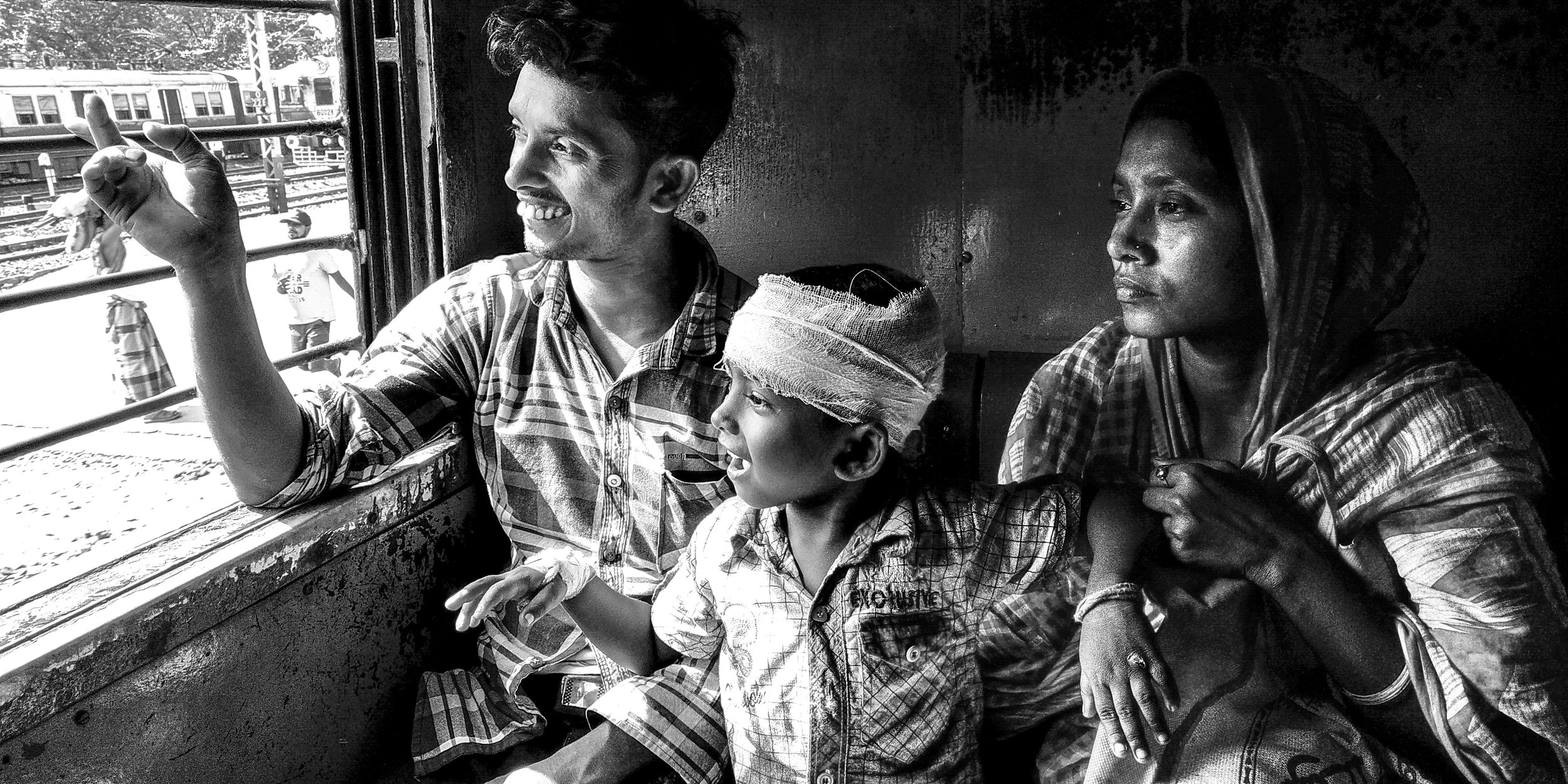 A father his showing his little boy something interesting outside the window and they are sharing the laughter. This family was sitting front of my sit in the Canning Local Train. The little boy is suffering in Head injury. Dad was very worried, but the boy was looking at his father's face occasionally, the father was showing at various funny gestures showing him trees or other trains Date: 13 September, 2018