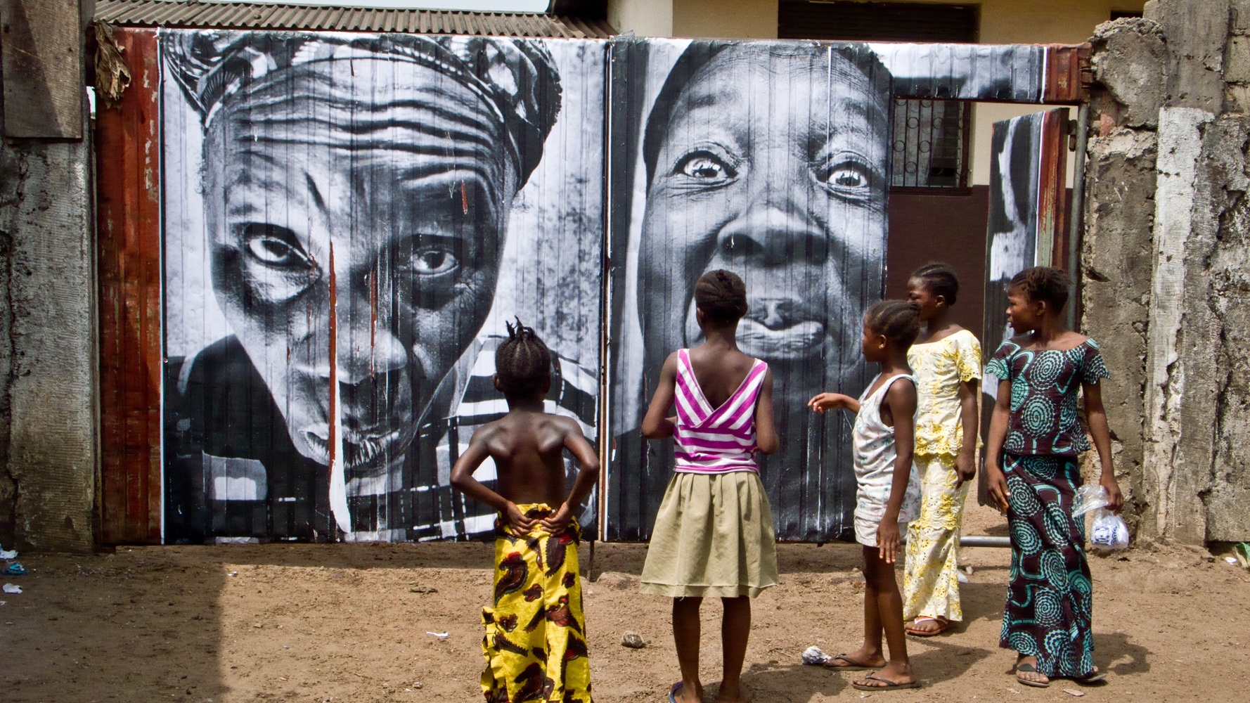 JR,  28 Millimétres; Women Are Heroes, Pasting in Monrovia streets, Liberia,  2008, Color photograph, matte plexiglass, aluminum, wood, 125 x 222 cm | 49 1/4 in x 7.3 ft. Courtesy of ©JR-ART.NET