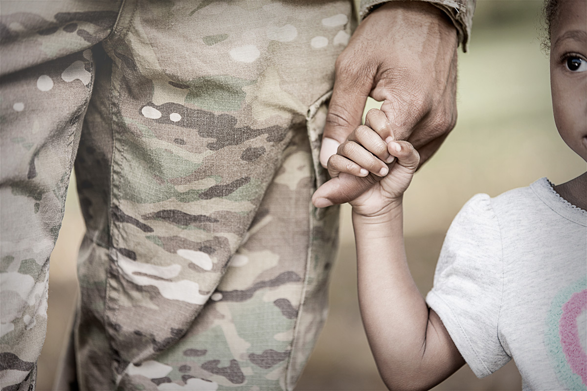 Image of veteran in uniform holding a young childs hand