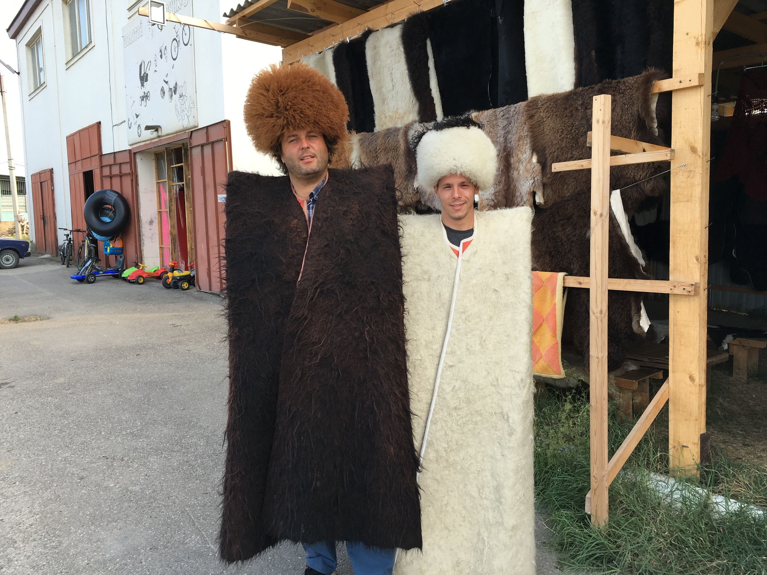 Vova and Mike trying some traditional fur clothing at a roadside stand selling furs.