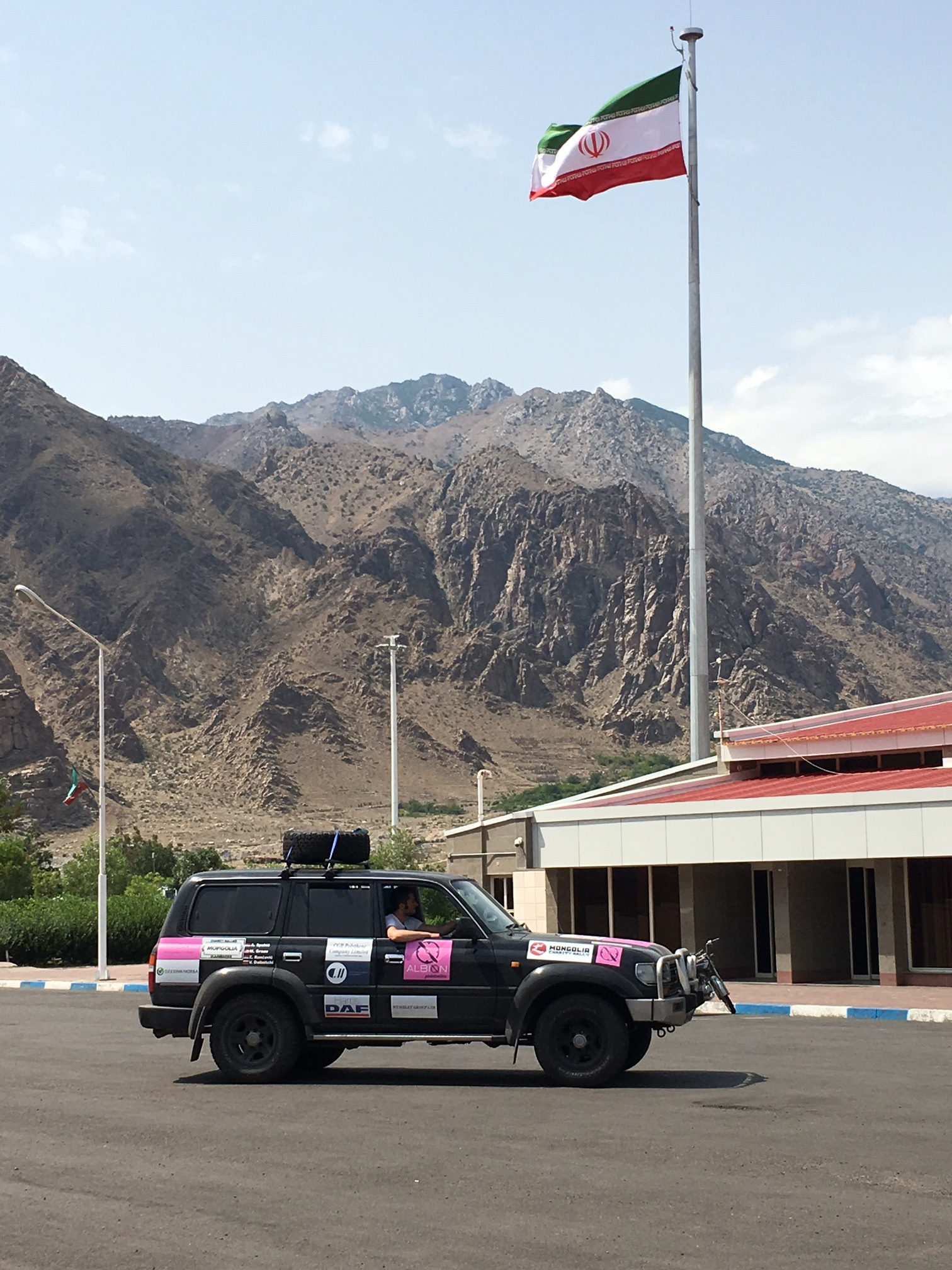 Our car under a giant Iranian flag at the border