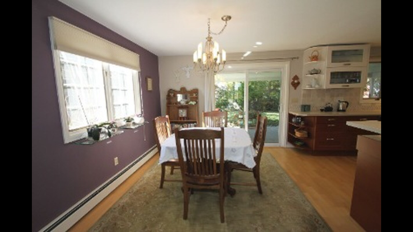 Kitchen: I love the slider that goes to the back porch but the purple painted accent wall has got to go! The floors were a fake wood that clashed with the orangish cabinetry.