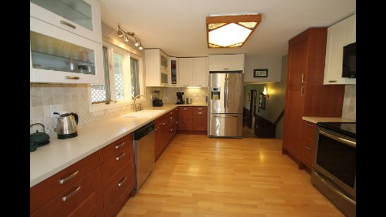 The kitchen had been updated with Ikea cabinetry but the overhead lighting and faux wood floors gave it an outdated look.