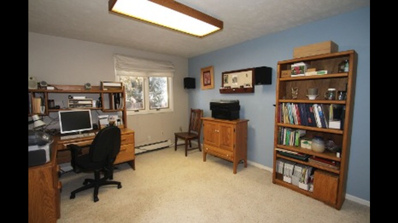 The office is on the lower level of the home with the family room and has a blue painted accent wall and old carpeting.