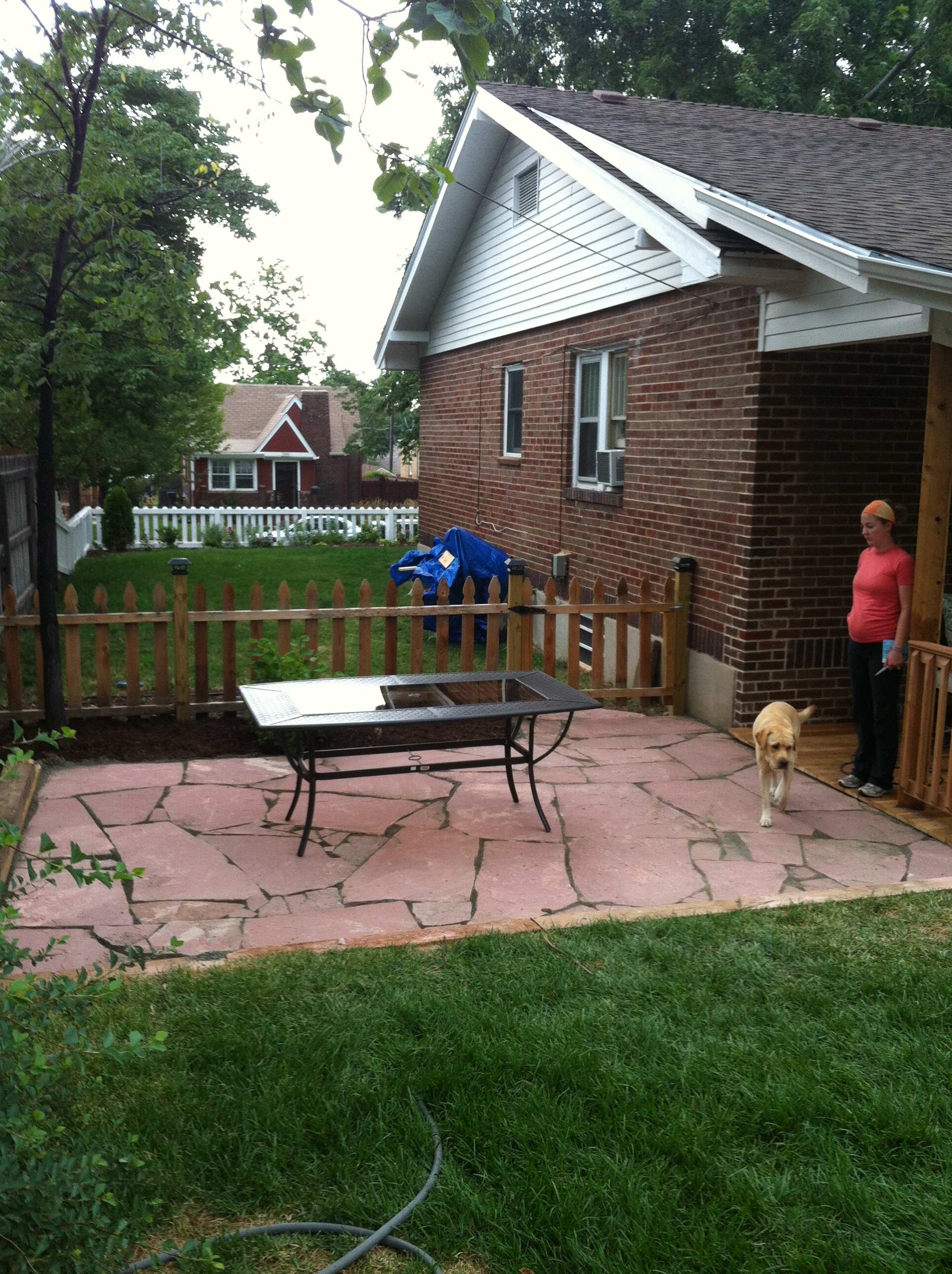 Progress shot of the new picket fence and flagstone patio in our backyard