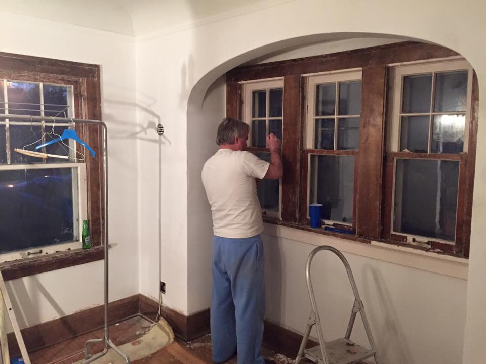 My dad scraping the paint off of one of the windows in the dining room