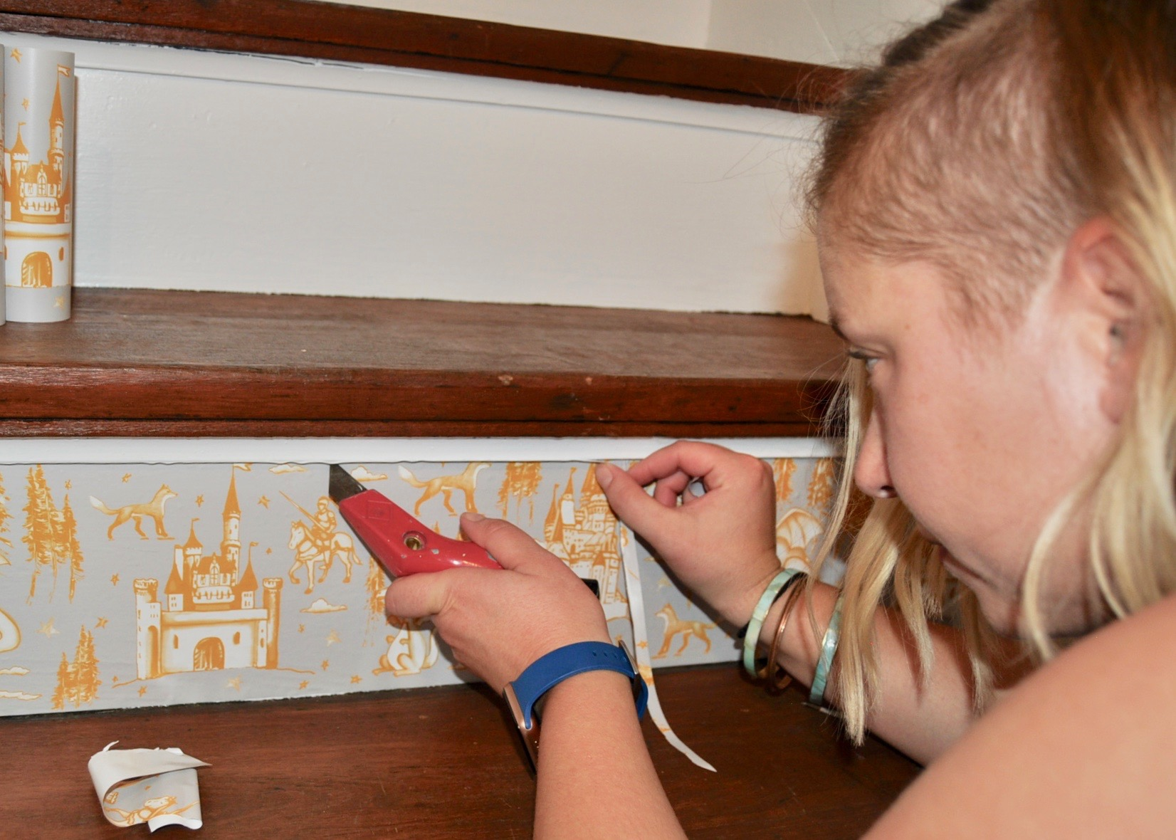 Removing the excess wallpaper with a utility knife.