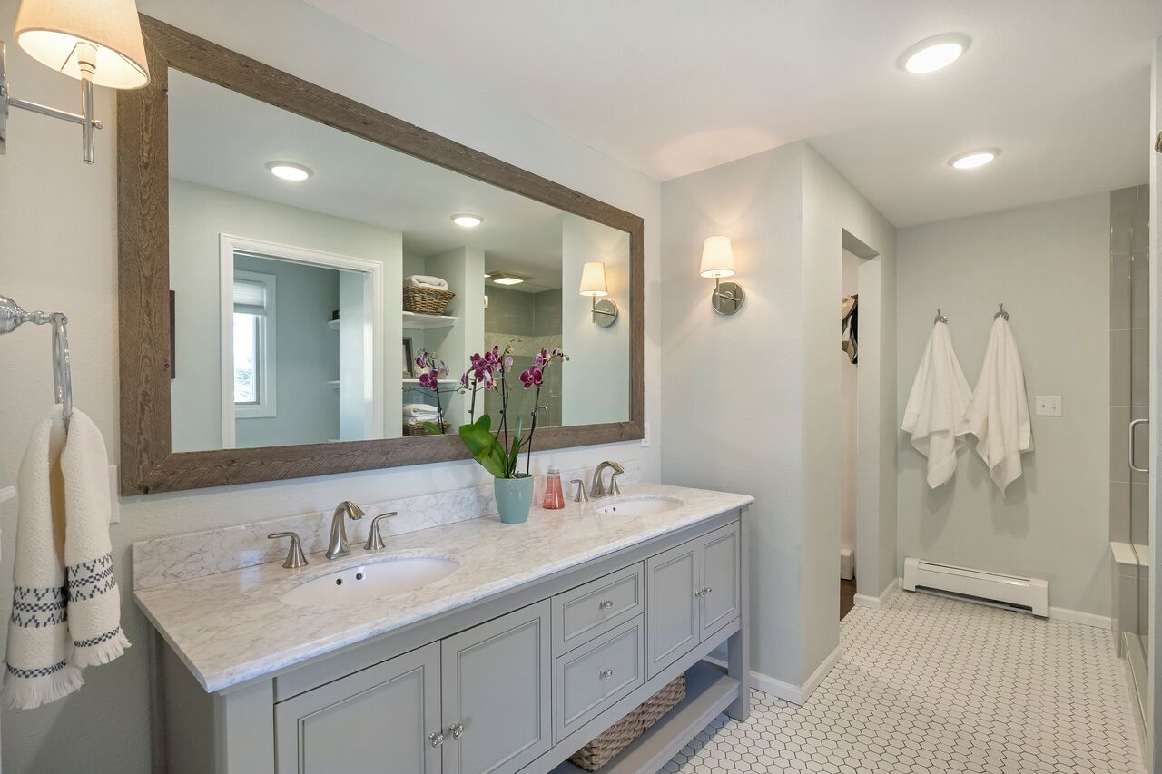 Master bathroom finished product with rustic wood trim around the mirror,